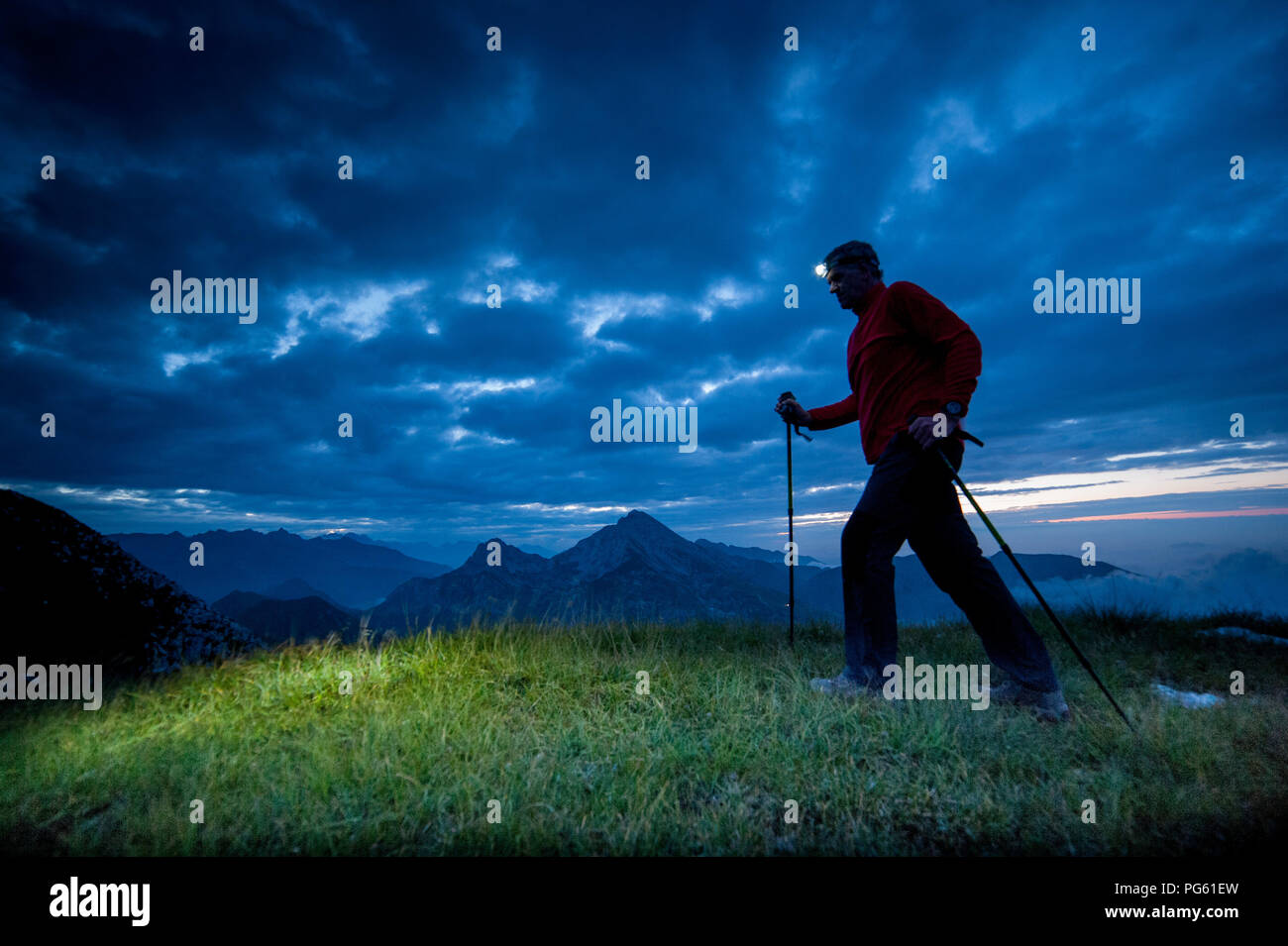 walk in the mountains with an early morning electric torch - Stock Image
