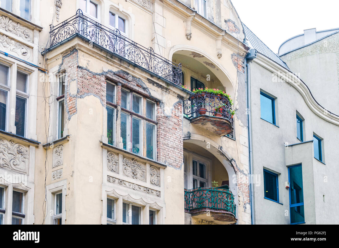 A dilapidated building with balconies and missing plaster showing exposed brick work in Poznań (Poznan), Poland - Stock Image