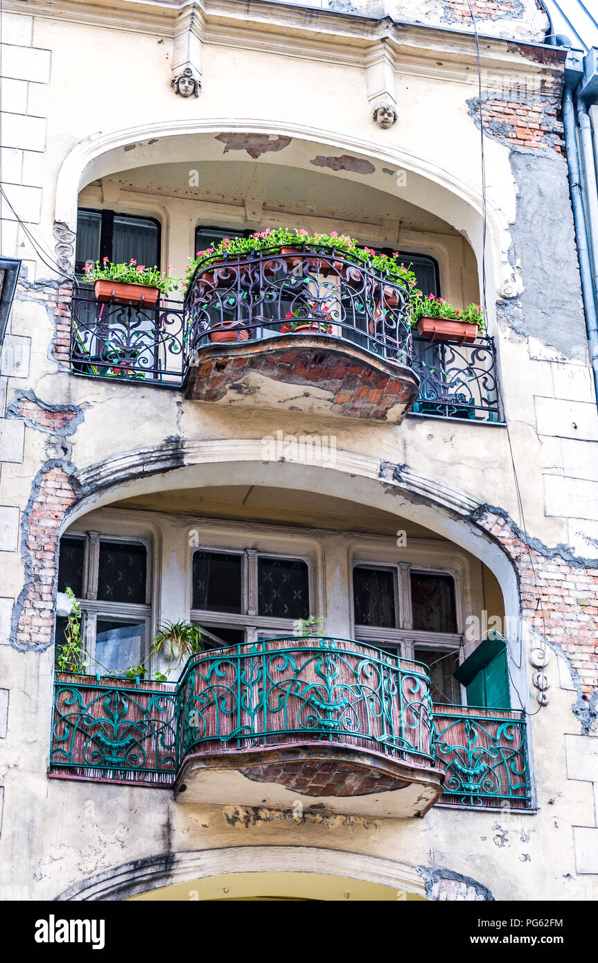 A dilapidated building with 2 balconies and missing plaster showing exposed brick work in Poznań (Poznan), Poland - Stock Image