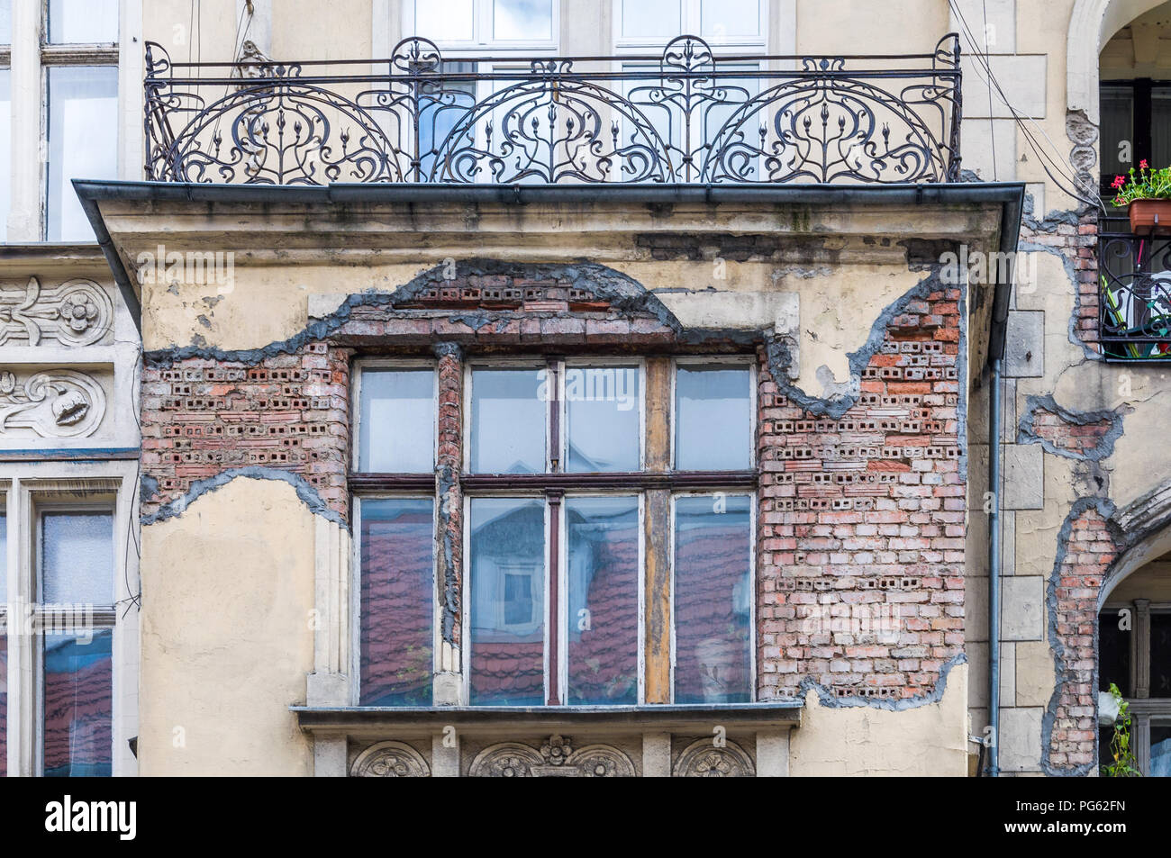 A dilapidated building with a balcony and missing plaster showing exposed brick work in Poznań (Poznan), Poland - Stock Image