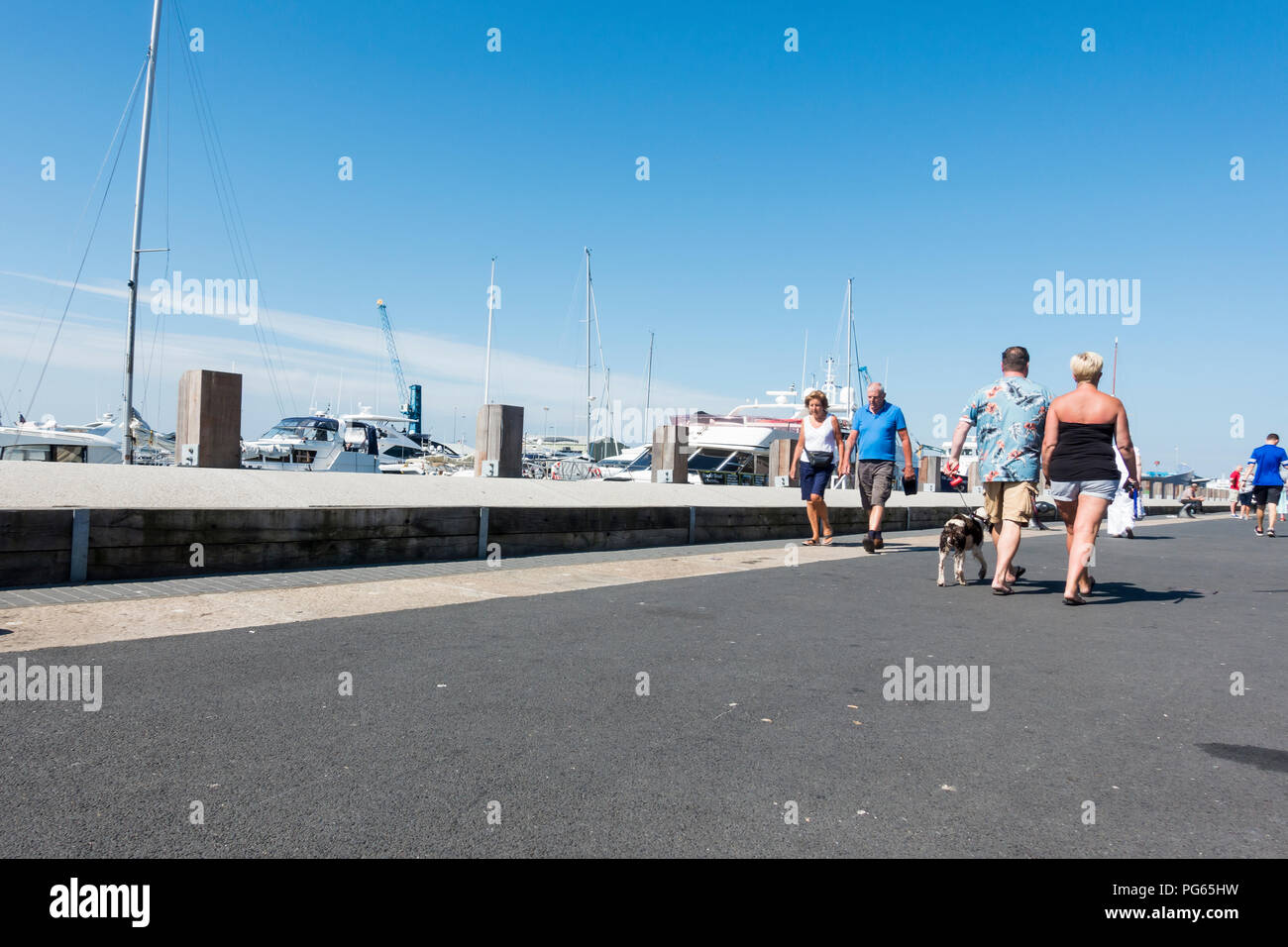 People walking along Poole Quay on a warm sunny day, Poole, Dorset, UK - Stock Image