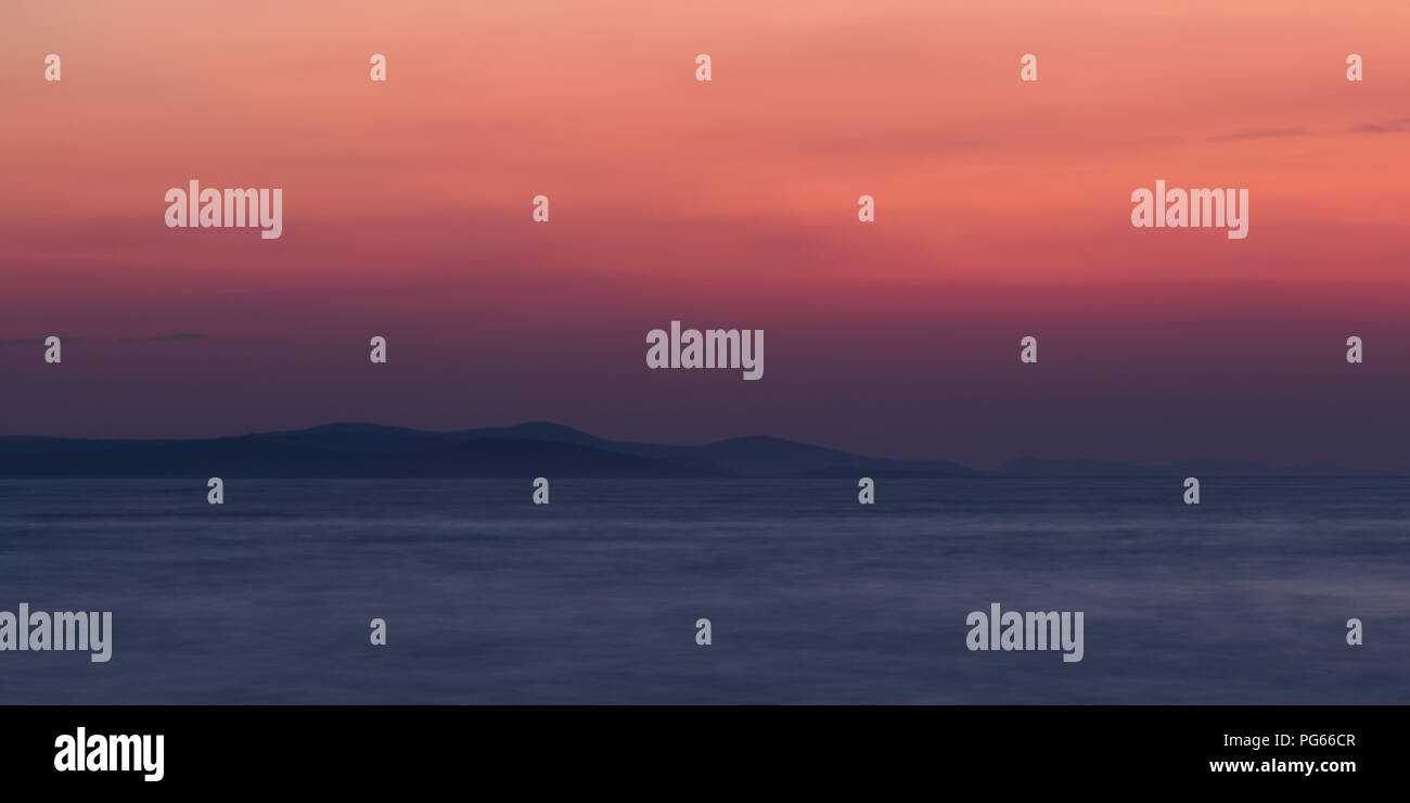 Seascape from Zadar's boardwalk and sea organ in the Croatian coast after sunset during summer. Colourful gradient sky and distant land features. - Stock Image