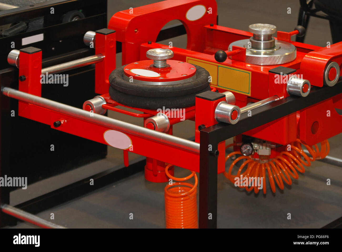Pneumatic air lift jack in auto service garage - Stock Image