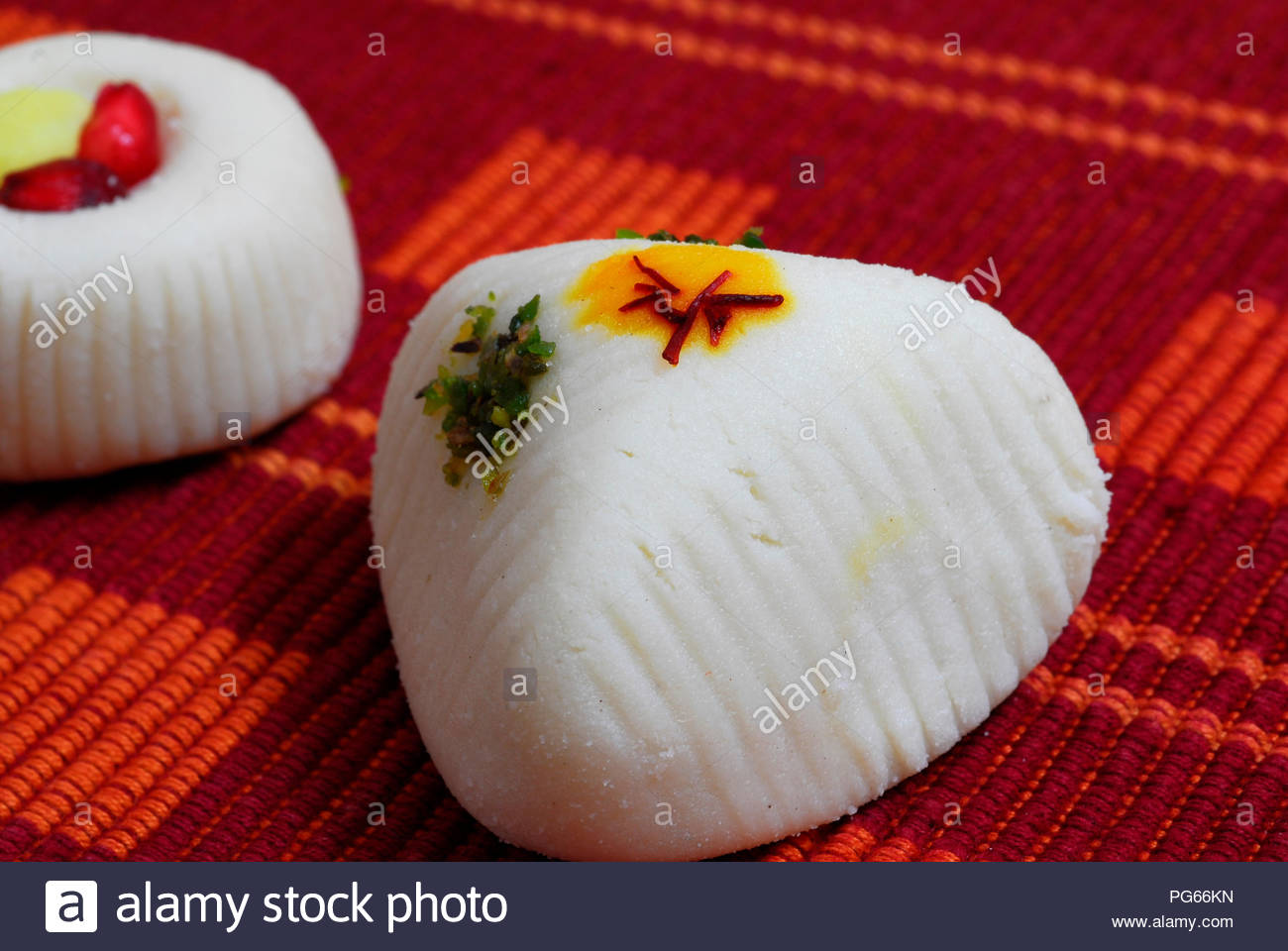 An isolated shot of White Indian Sweets Mithai decorated with saffron - Stock Image