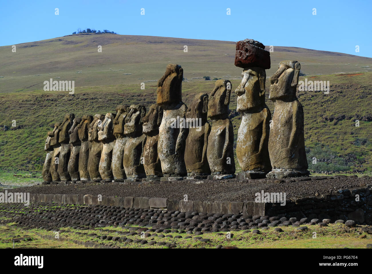 The giant Moai statues of Ahu Tongariki with Poike volcano in background, Archaeological site in Easter Island, Chile - Stock Image