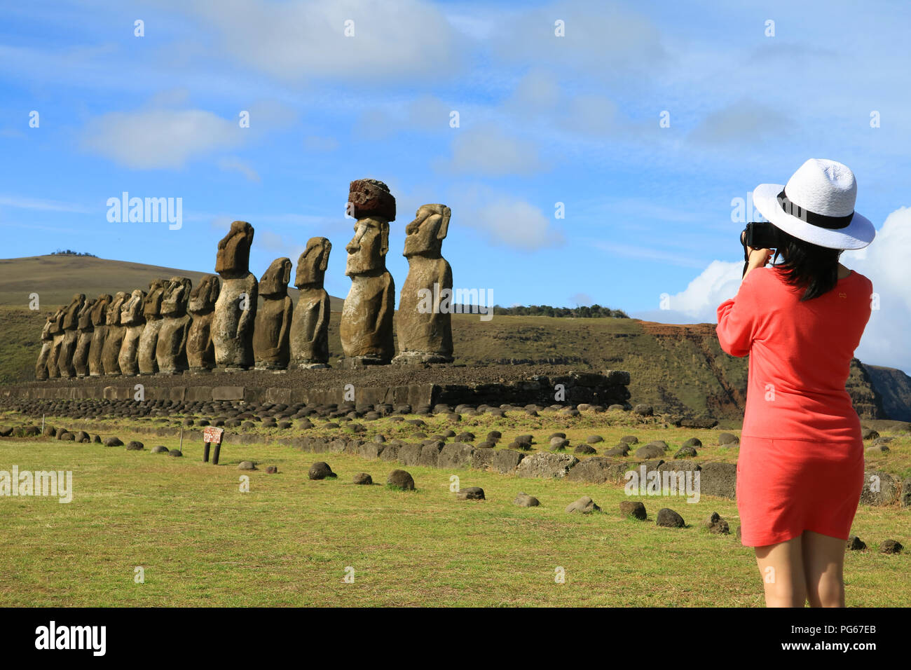 Young woman taking pictures of the famous Moai statues at Ahu Tongariki on Easter Island, Archaeological site in Chile - Stock Image