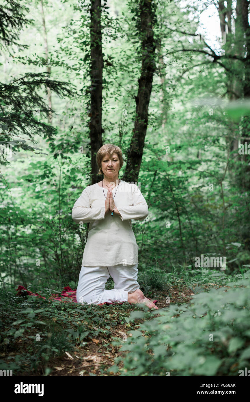 Senior woman doing yoga - Stock Image