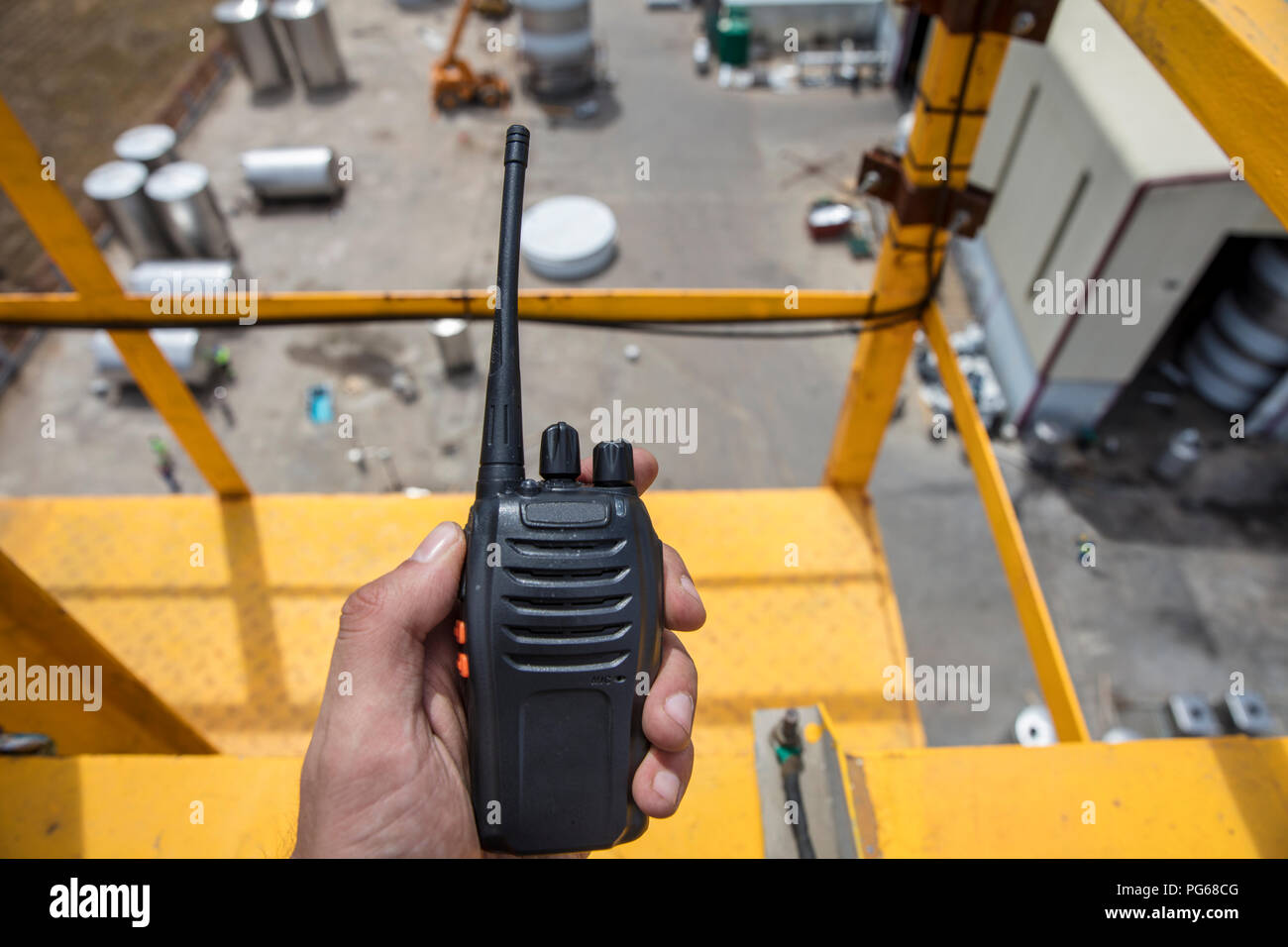 Hand holding walkie talkie on top of a crane on construction site Stock Photo