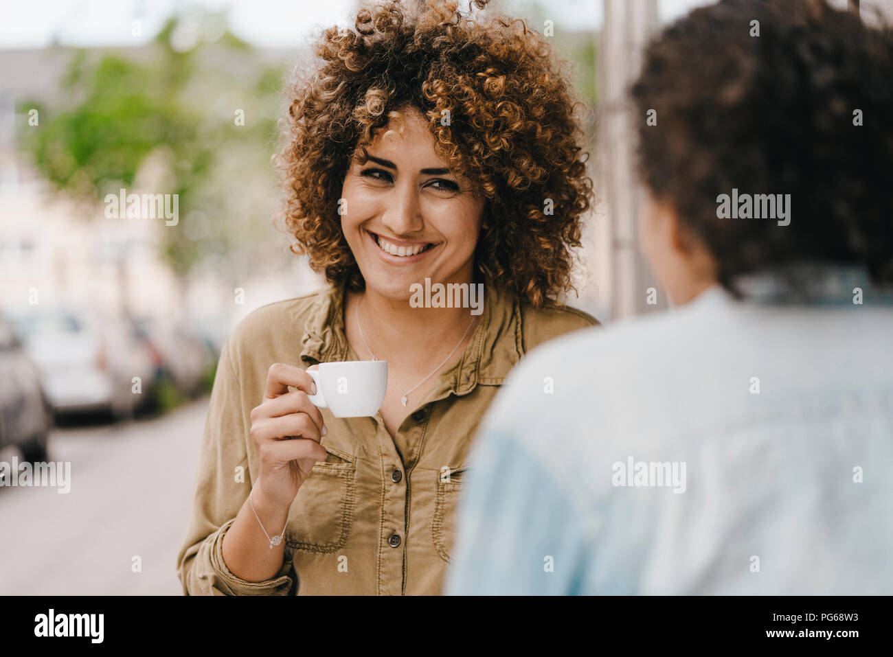 Two friends drinking coffee, exchanging news - Stock Image