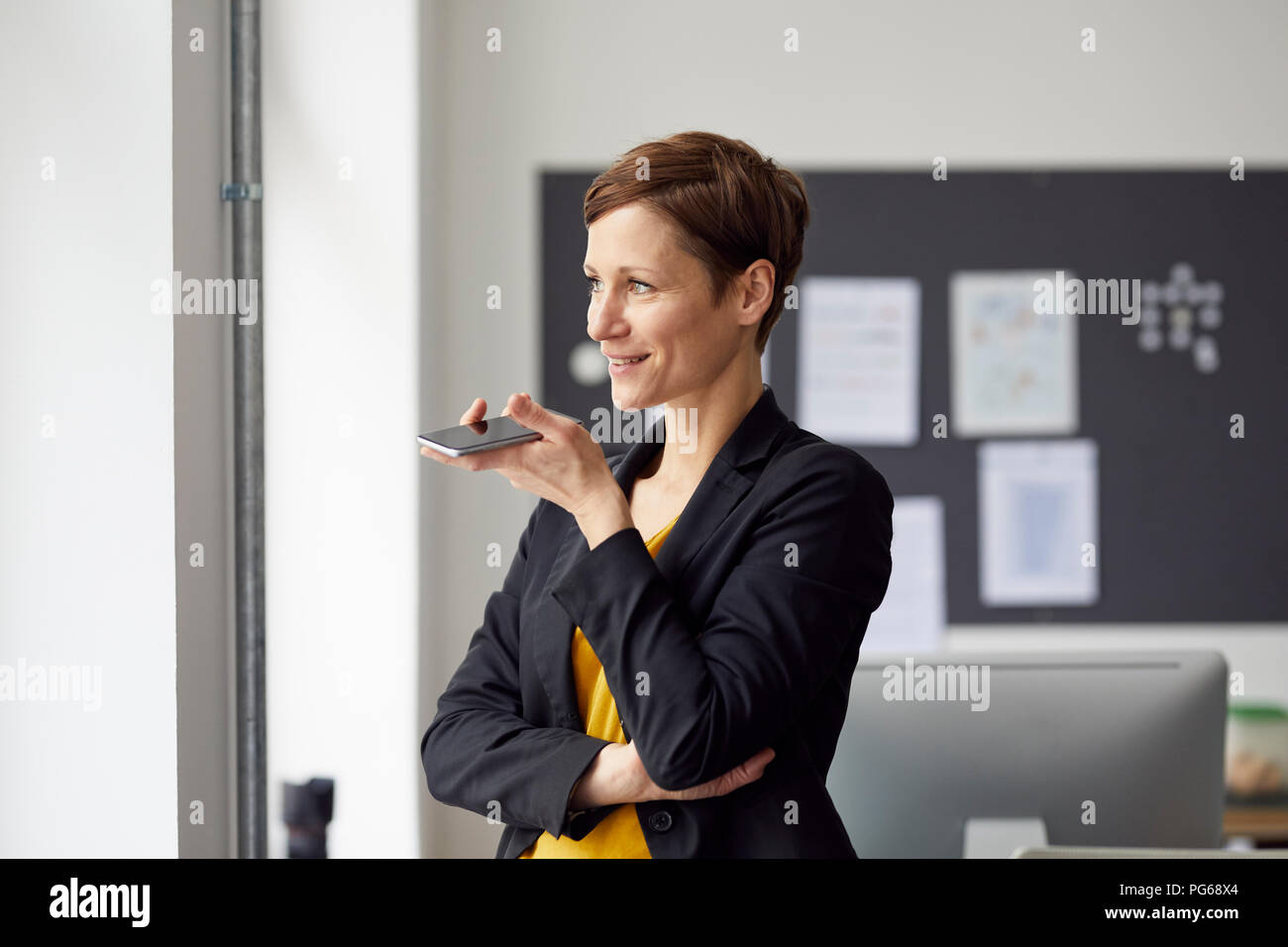 Attractive businesswoman standing in office, using smartphone - Stock Image