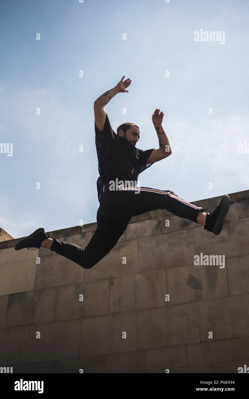 Tattooed man doing parkour - Stock Image