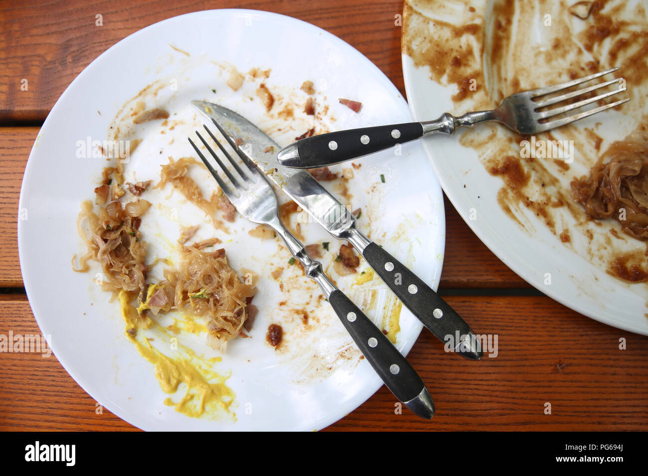 Leftovers plate with cutlery on wooden table - Stock Image