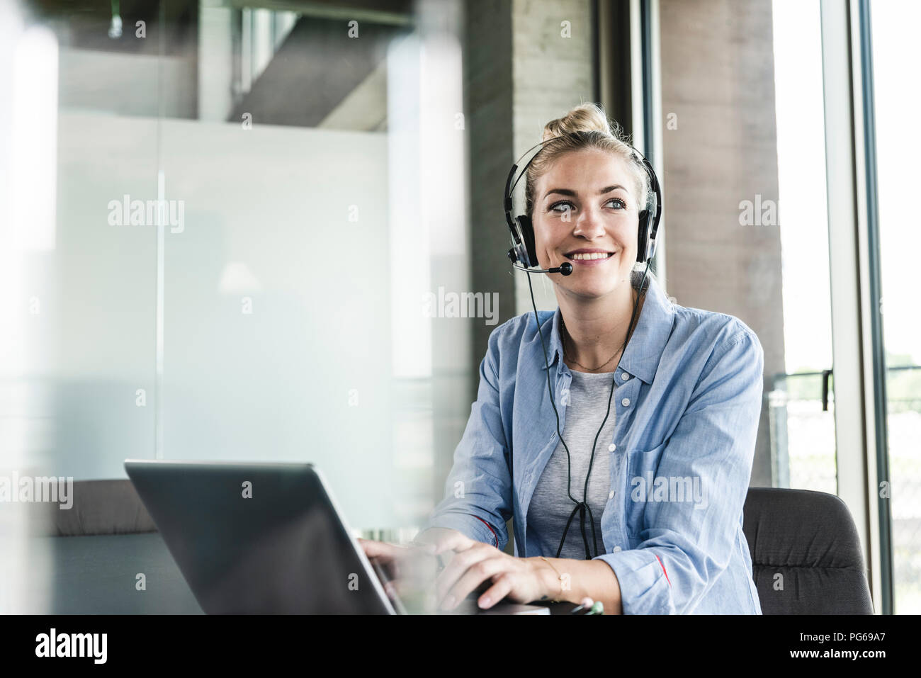 Young businesswoman sitting at desk, making a call, using headset and laptop - Stock Image