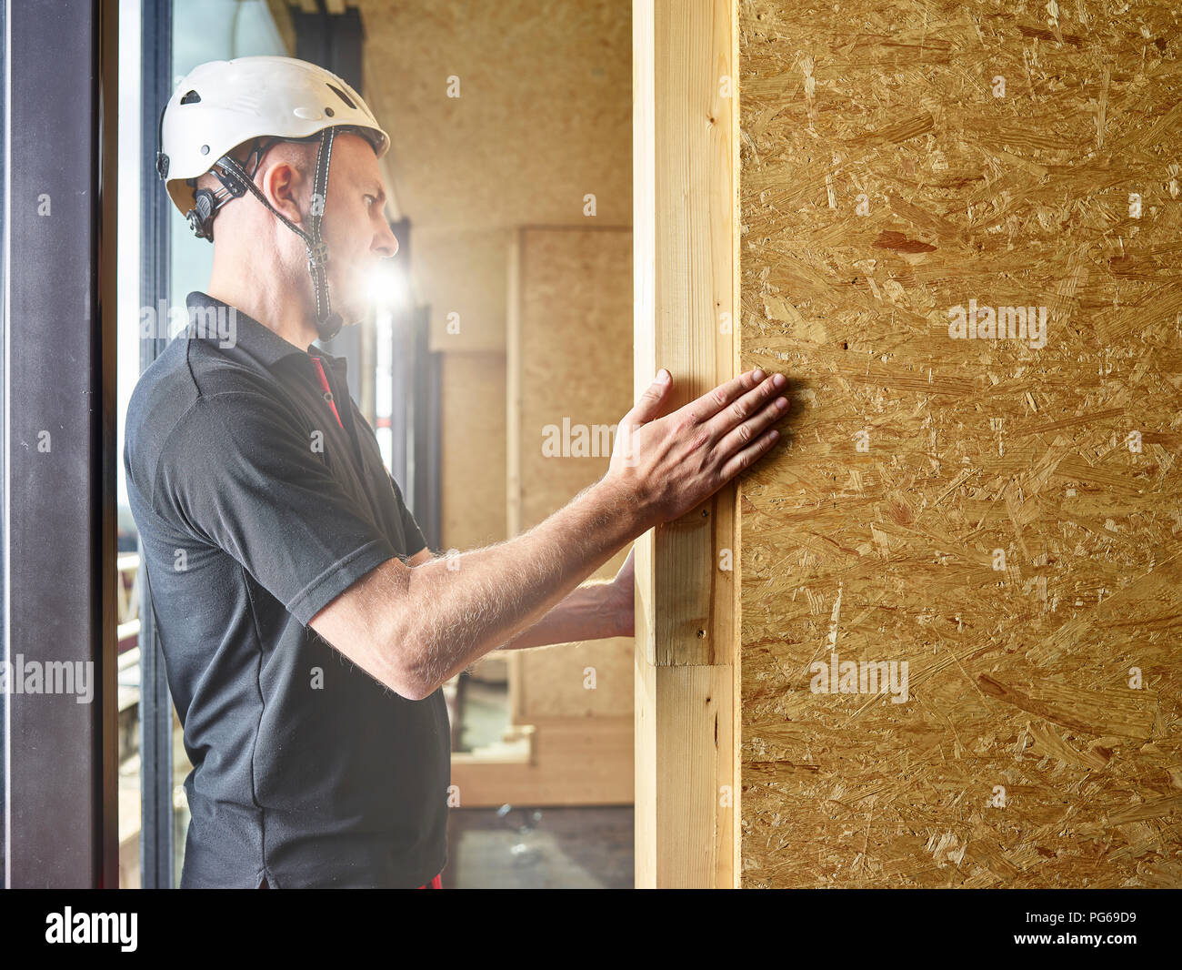 Worker with helmet working with flakeboard - Stock Image