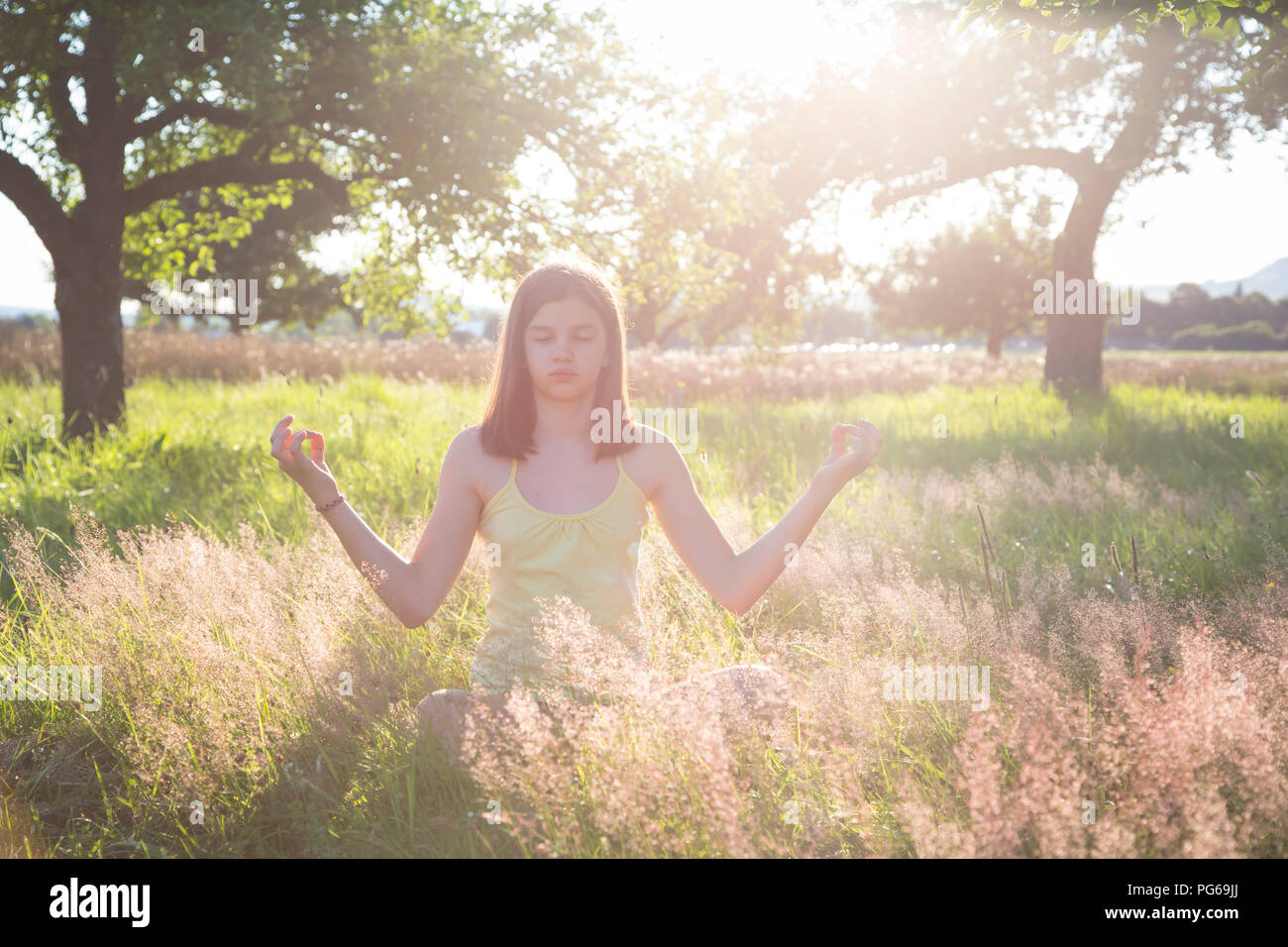 Young girl meditating on meadow at summer evening - Stock Image