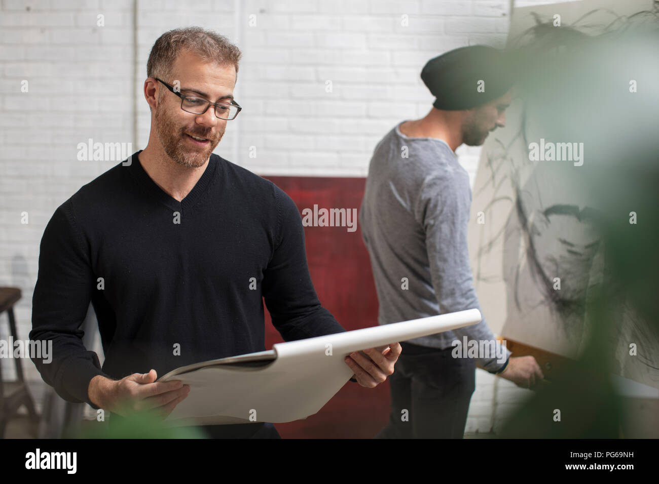 Smiling man looking at sketchbook in artist's studio - Stock Image