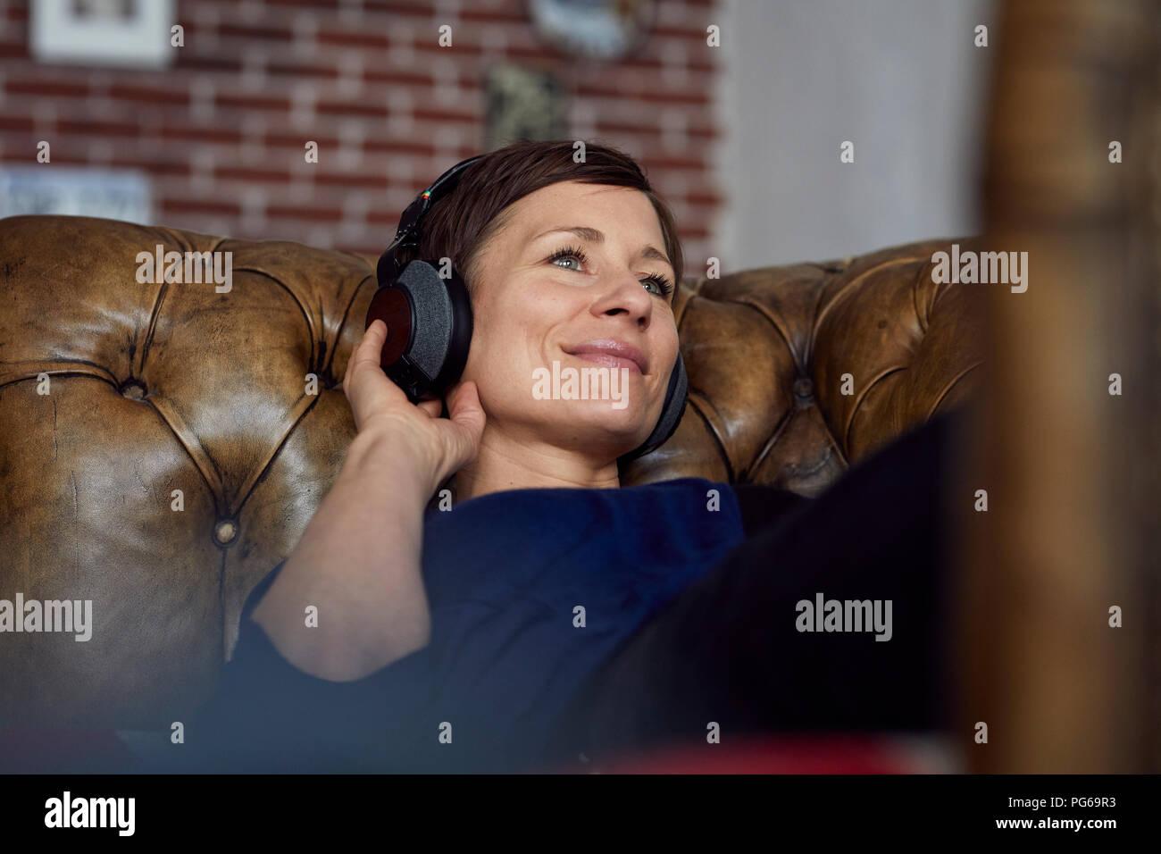 Woman with headphone lying on sofa, listening music - Stock Image