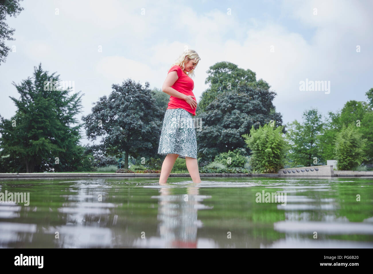Pregnant woman walking through pond in park - Stock Image