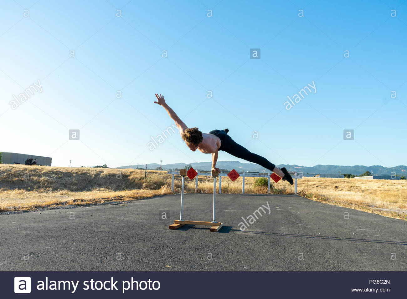 Acrobat balancing on handstand canes - Stock Image