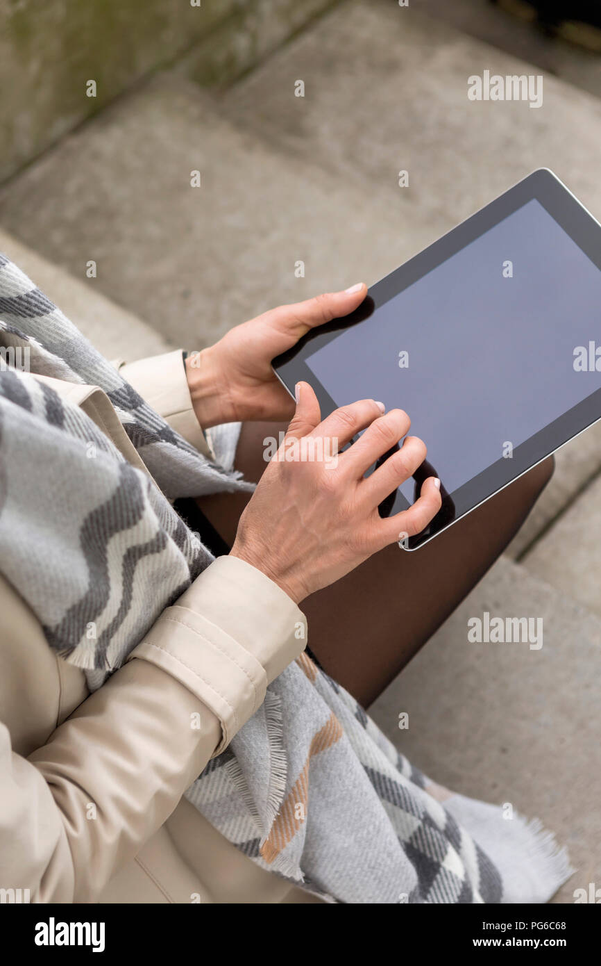 Woman using digital tablet, partial view - Stock Image