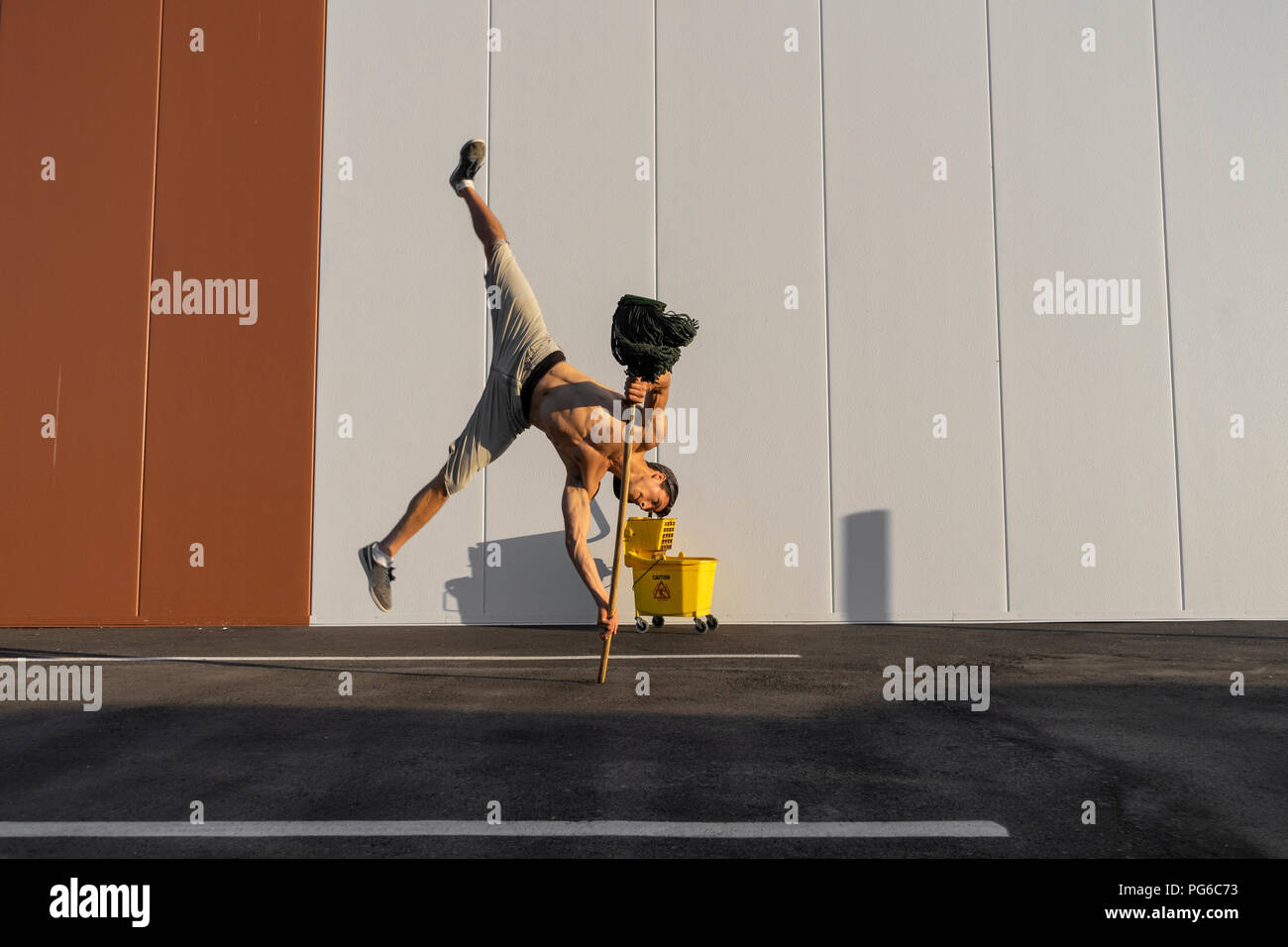 Acrobat playing with cleaning bucket and mop - Stock Image