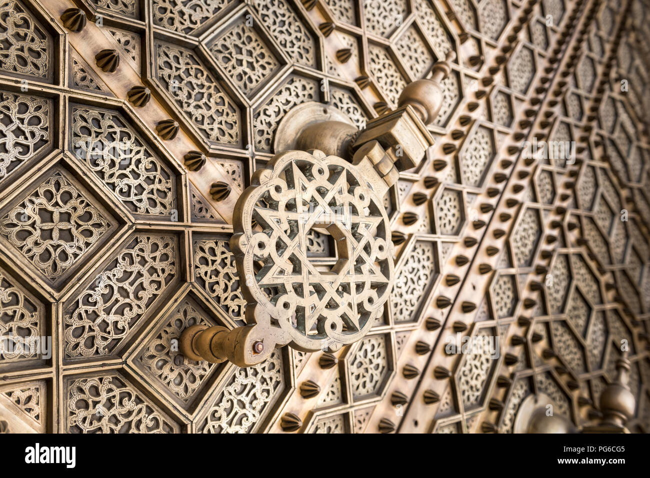 Close up angled view of a large brass door knocker on the exterior of Mosque Hassan in Rabat, Morocco - Stock Image