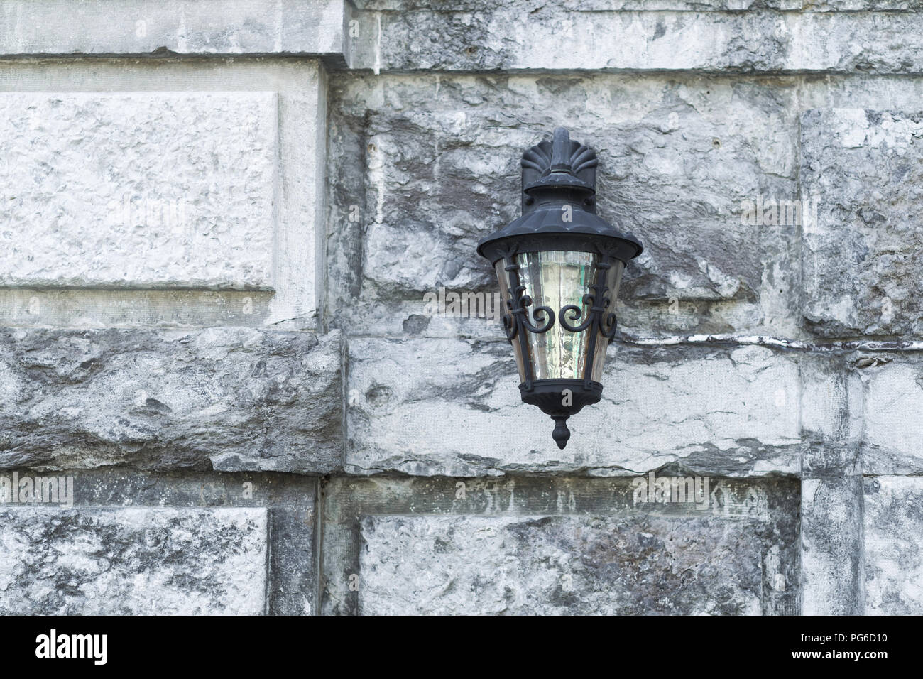 Old black iron lamp on stone wall of middle ages castle - Stock Image