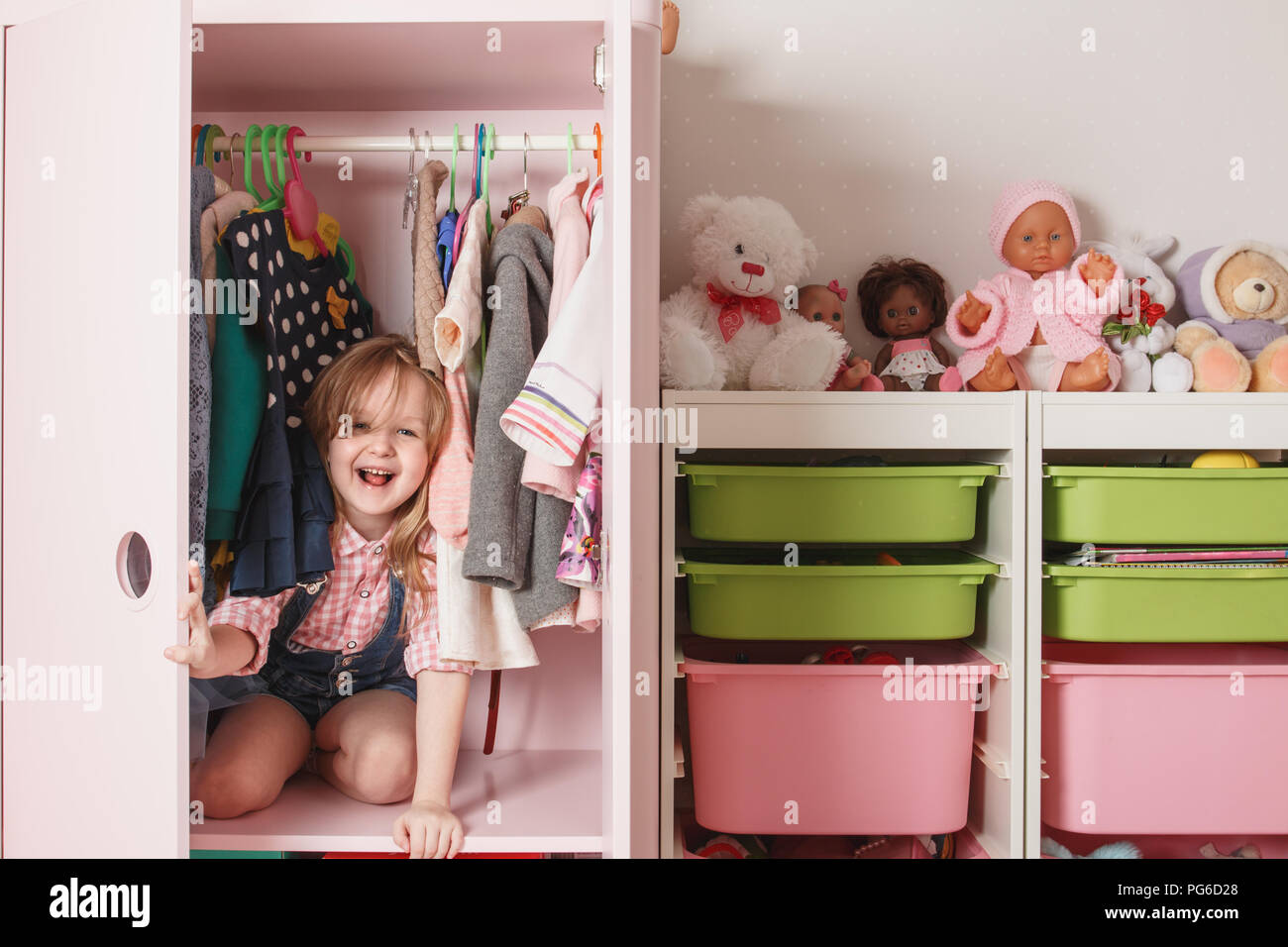 A little girl is sitting in a wardrobe with a children's department. Storage system for children's things Stock Photo