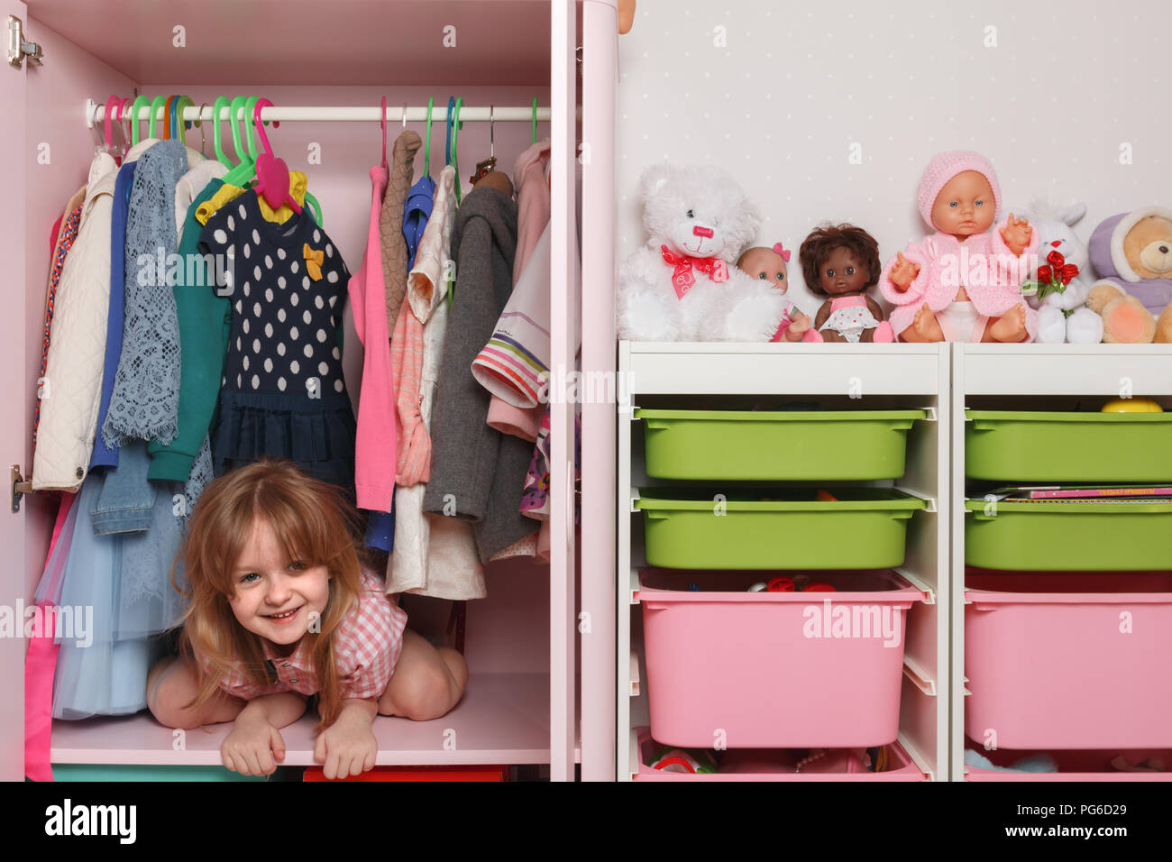 A little girl is sitting in a wardrobe with a children's department. Storage system for children's things - Stock Image