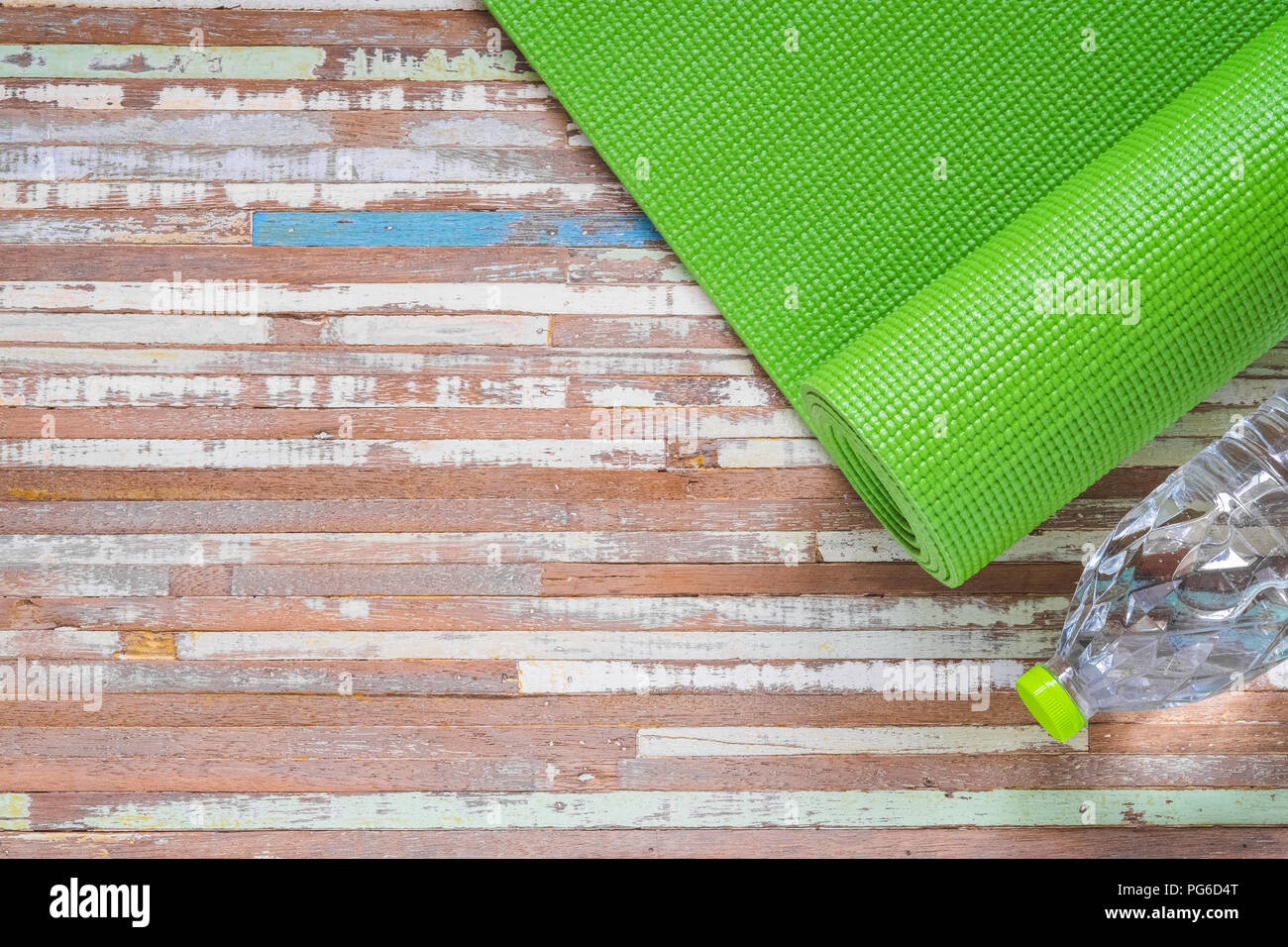 61f7a779d13b1 Green yoga mat on a wooden background with bottle of water, Top View with  copy space. Active healthy lifestyle background concept.