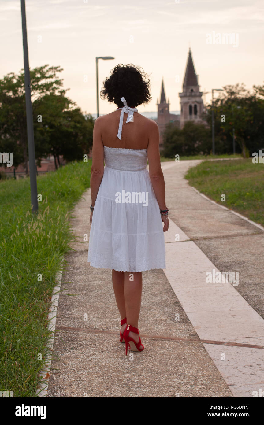 25e0784a2 Lady with short white dress and red shoes with heels, turned from  shoulders, with bare shoulders, while walking in a public garden towards  the city