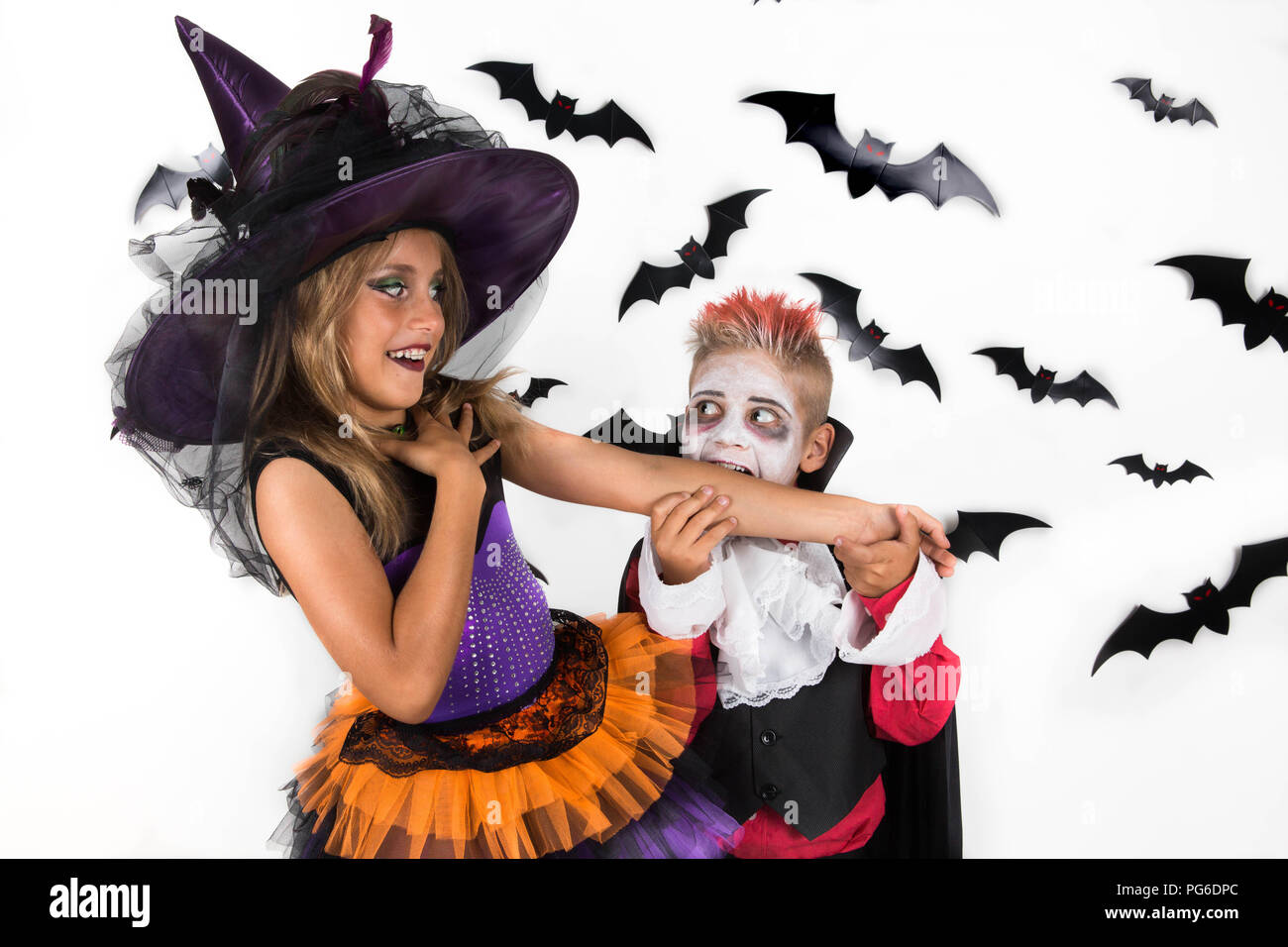 Kids celebrate Halloween in costumes of witch and vampire. Vampire pretends to bite witch's arm and she smiles in response. - Stock Image