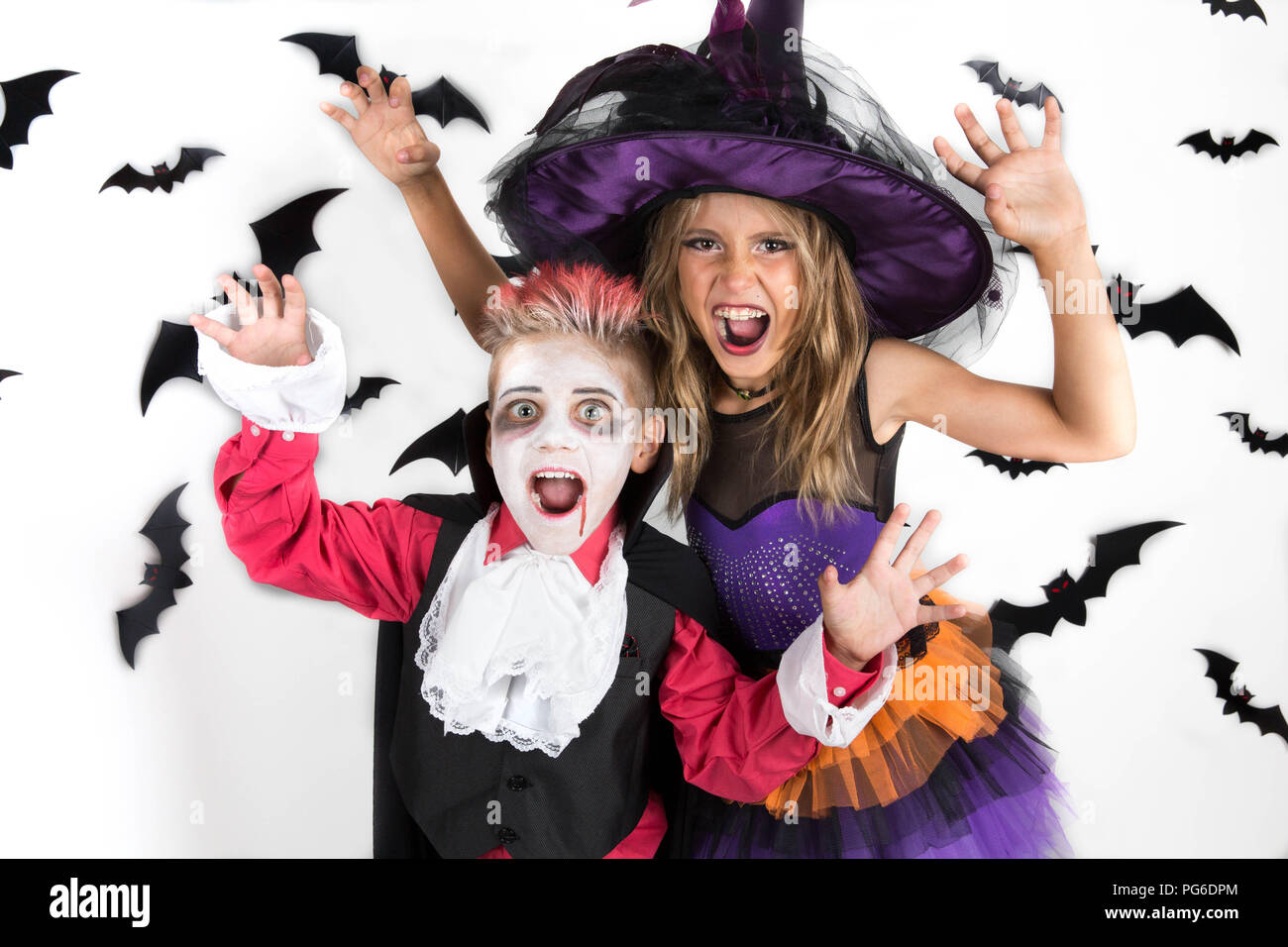 Halloween kids, Happy scary girl and boy dressed up in Halloween costumes of witch, sorcerer and vampire, Dracula for Halloween party or pumpkin patch Stock Photo