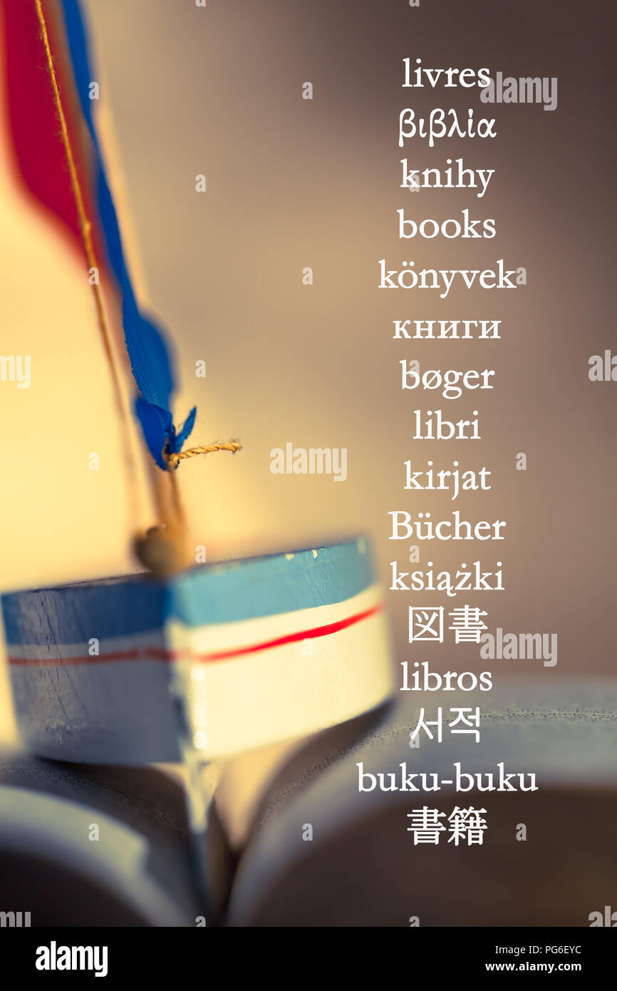 """The word """"books"""" written in different languages at background picture with toy sailboat between the wavy pages of open book Stock Photo"""