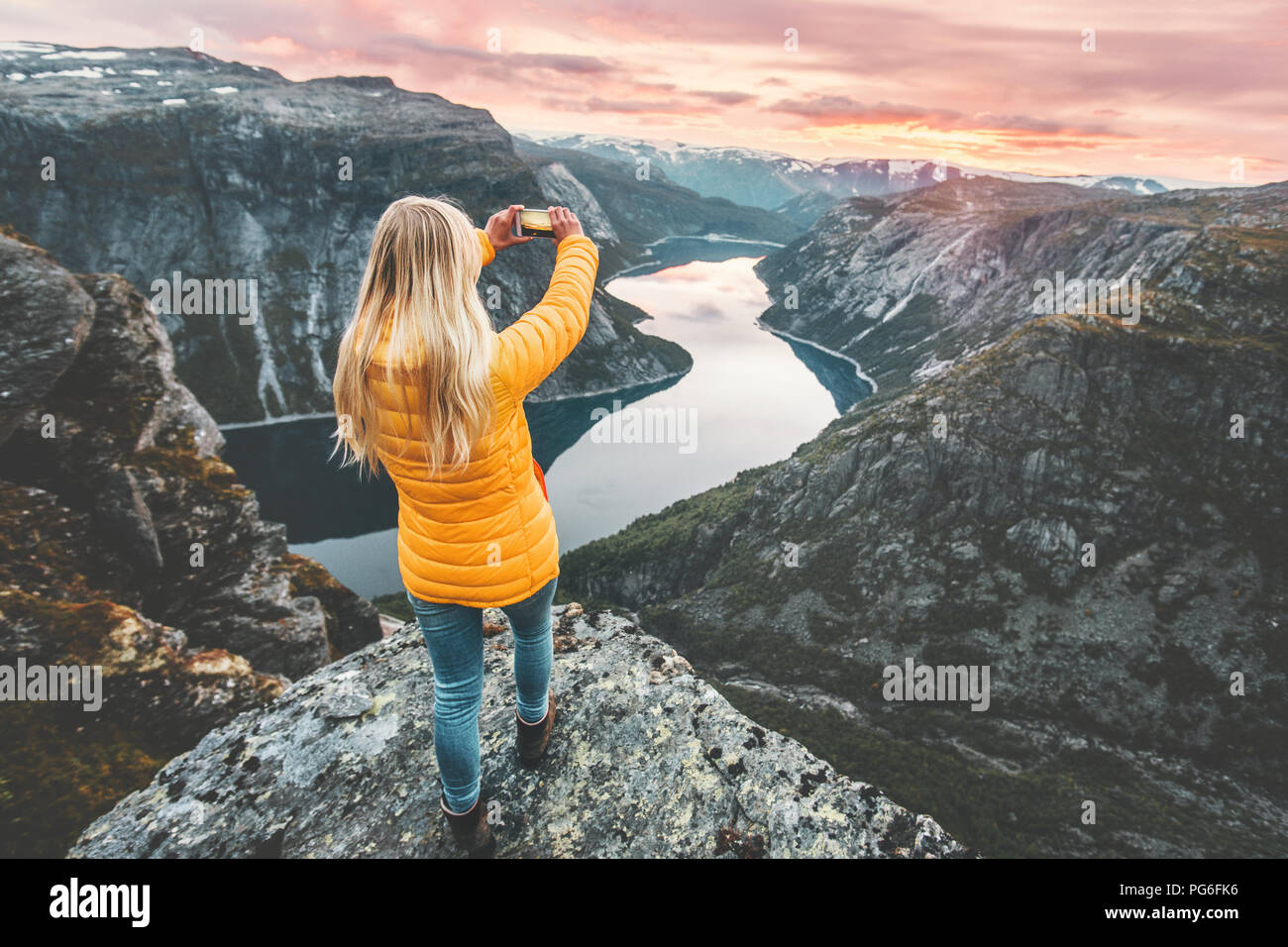 Woman taking photo by smartphone on mountain cliff over lake traveling in Norway adventure lifestyle active vacations modern technology connection con - Stock Image