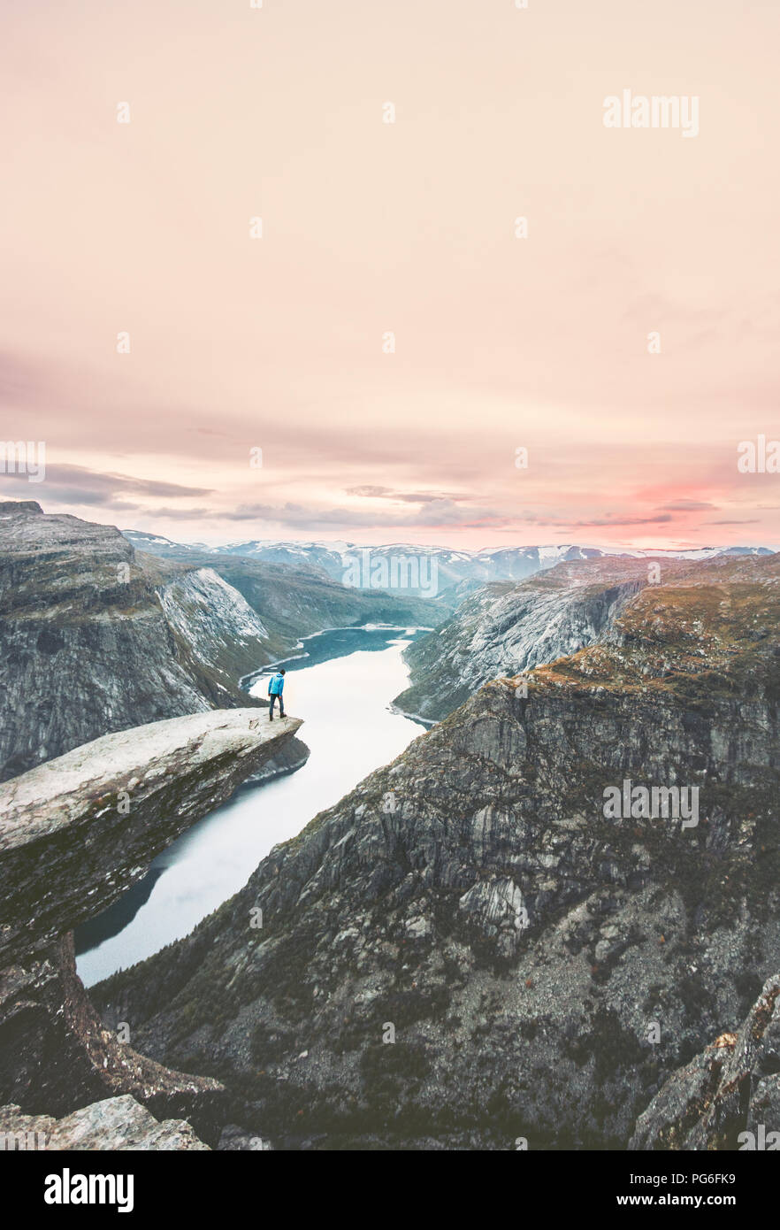Traveler man on the edge of Trolltunga cliff  traveling in Norway adventure lifestyle extreme vacations outdoor rocky mountains over clouds landscape  - Stock Image