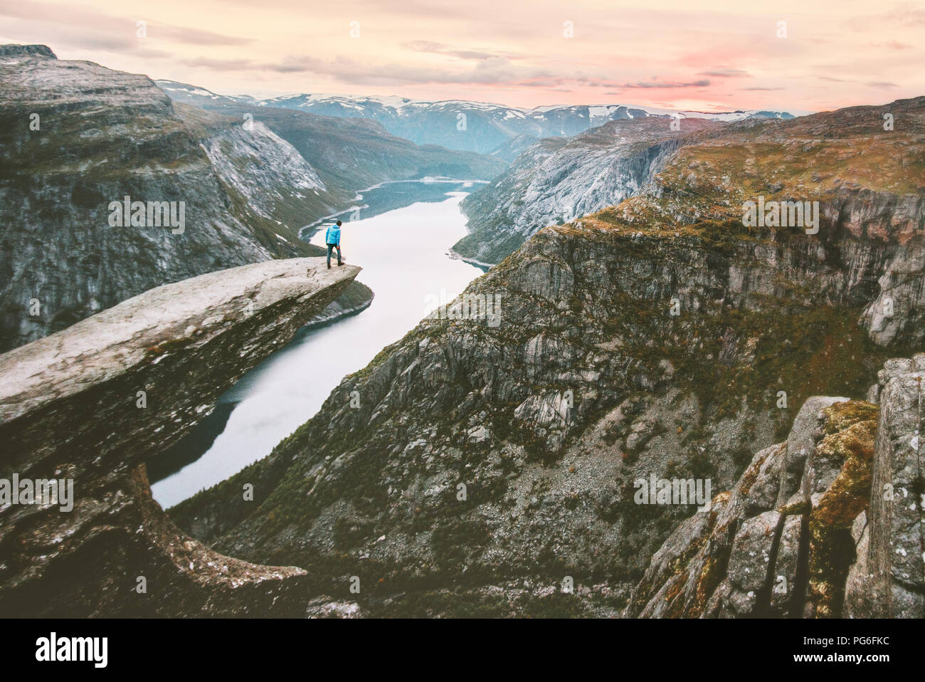 Traveler alone on the edge of Trolltunga cliff travel in Norway adventurous lifestyle extreme journey vacations outdoor  mountains over clouds landsca - Stock Image