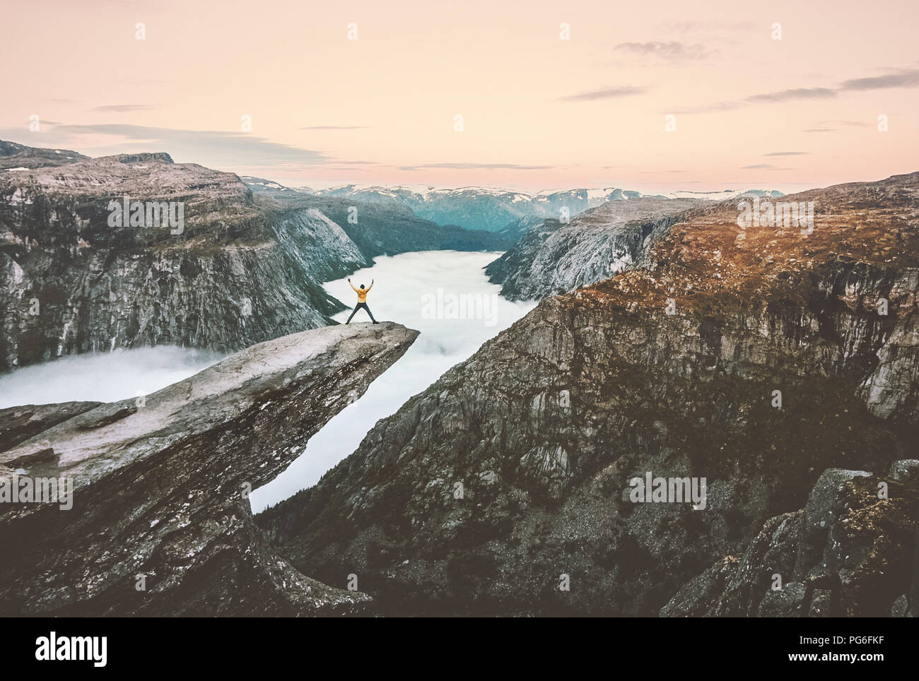 Man jumping on the edge of Trolltunga cliff  traveling in Norway adventure extreme trip vacations lifestyle tourism outdoor rocky mountains over cloud - Stock Image