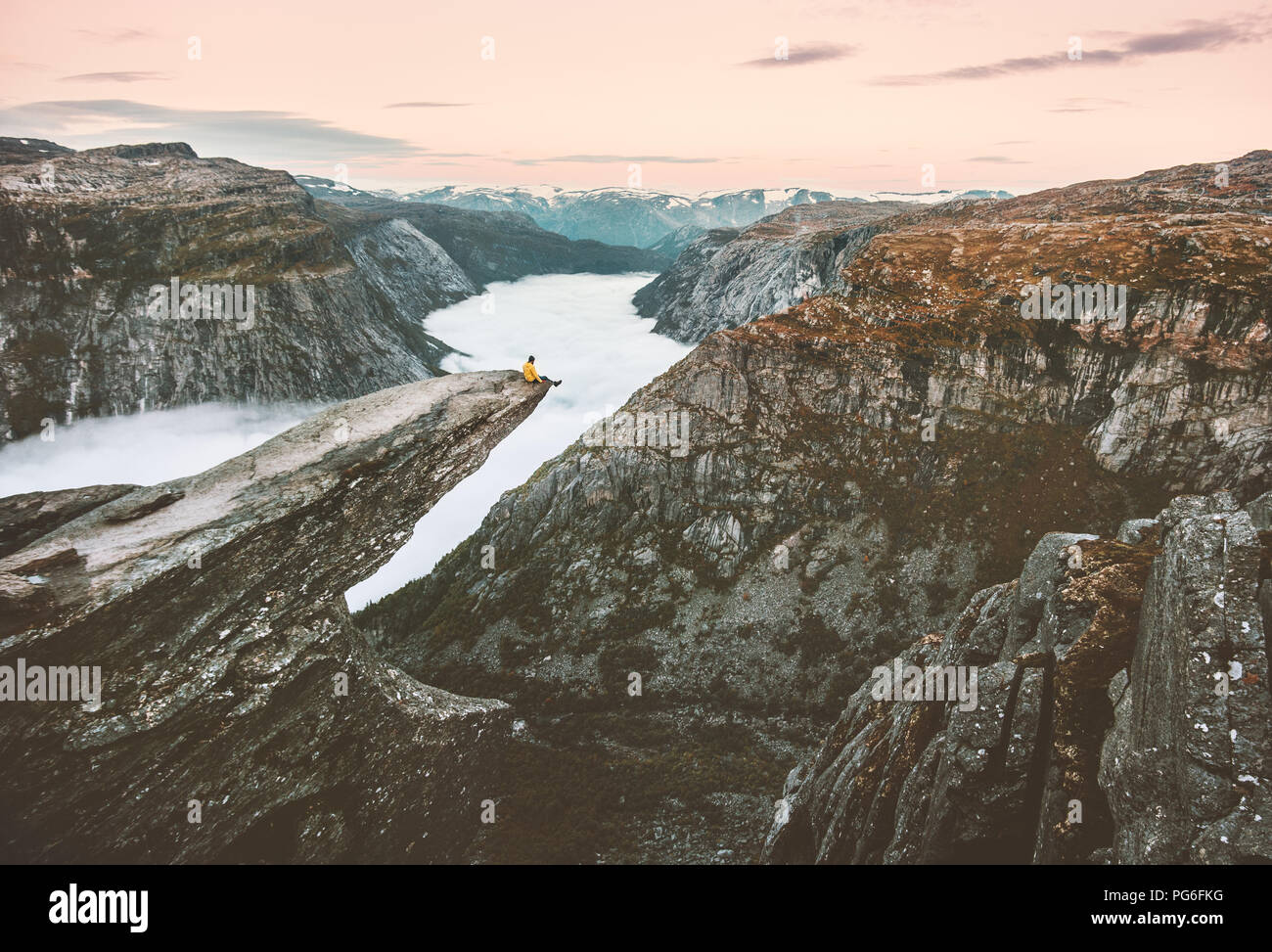 Traveler man sitting alone on the edge of Trolltunga cliff traveling in Norway adventure lifestyle extreme trip vacations outdoor mountains over cloud - Stock Image