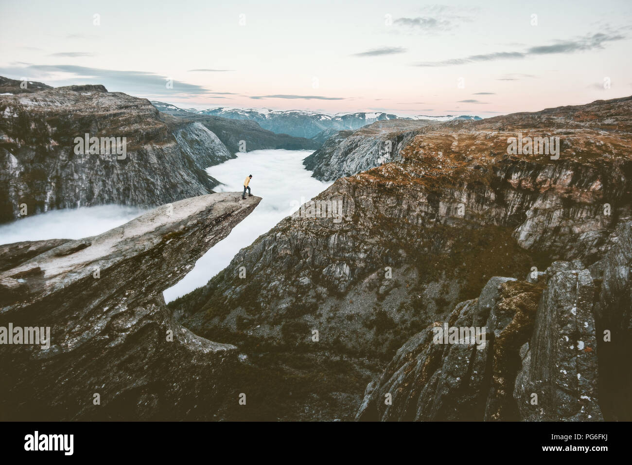 Traveler on the edge of Trolltunga cliff  traveling in Norway adventure lifestyle extreme trip vacations outdoor rocky mountains over clouds landscape - Stock Image