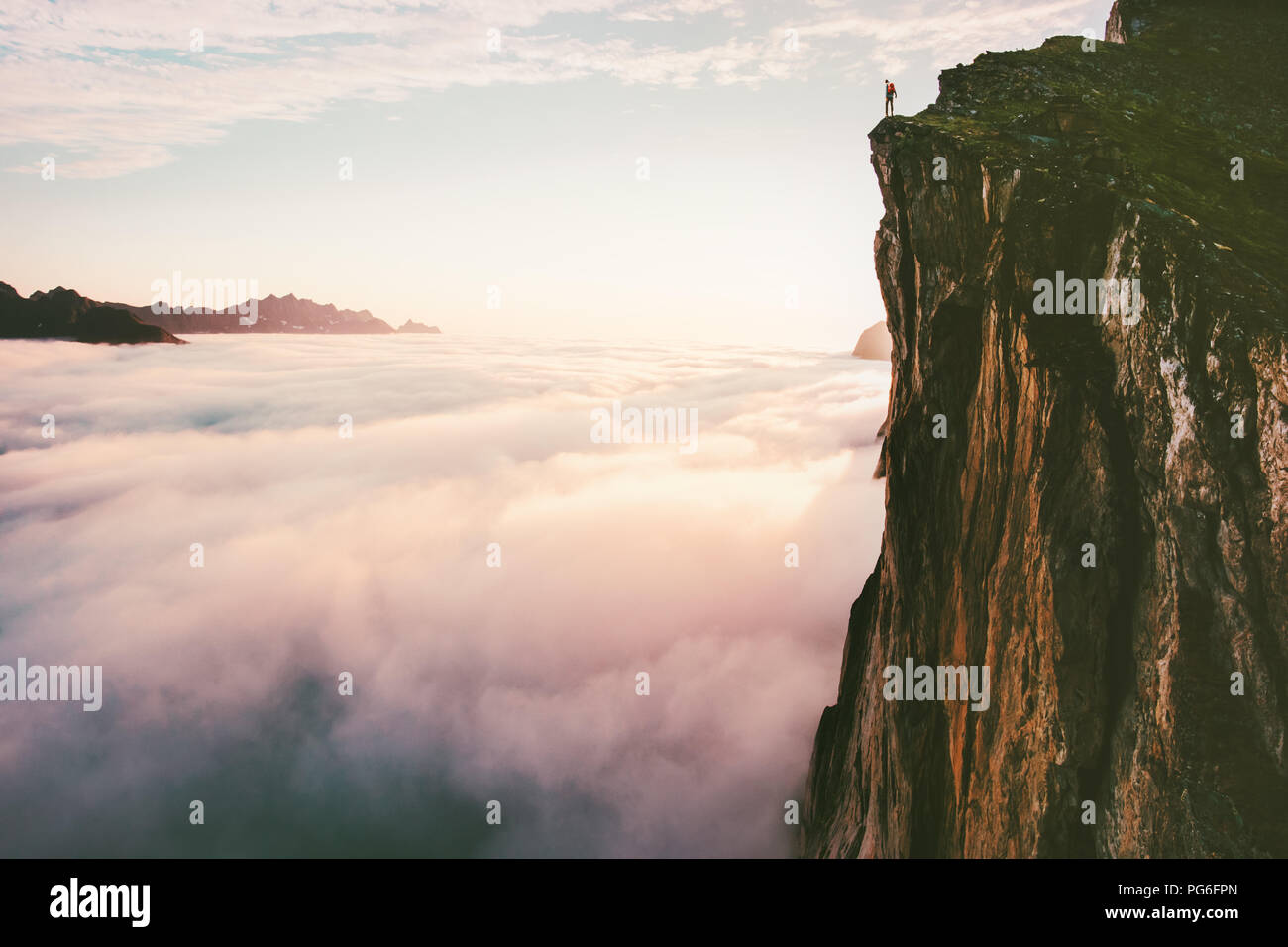 Traveler standing on cliff edge mountain top above sunset clouds travel adventure lifestyle summer journey vacations - Stock Image