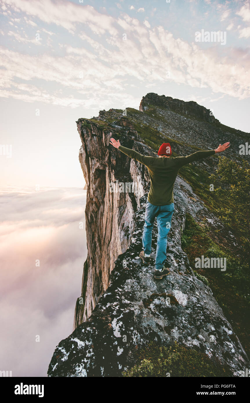 Adventurer man on the edge mountain ridge above clouds travel extreme lifestyle vacations outdoor - Stock Image