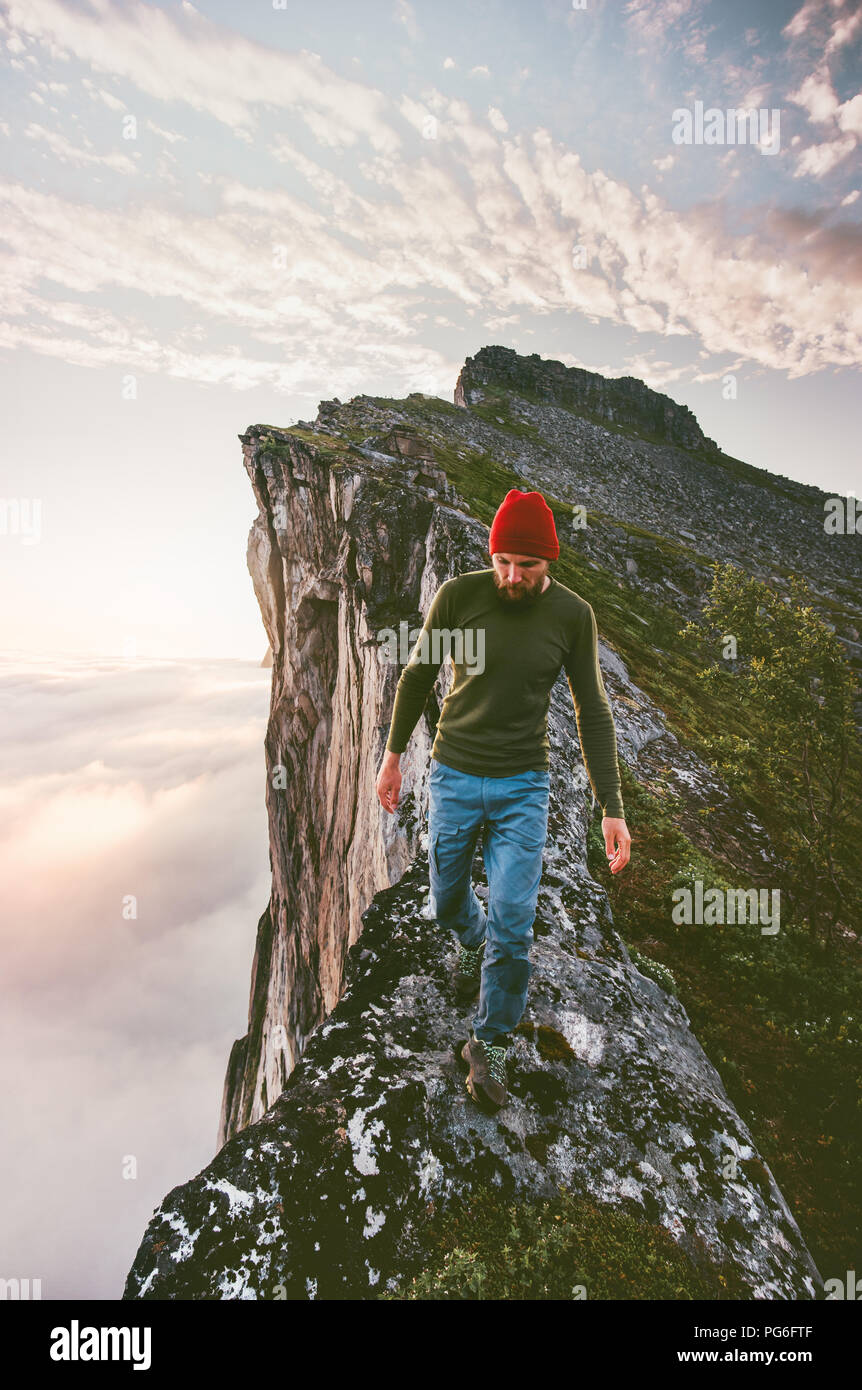 Man walking alone on the edge mountain ridge above clouds travel adventure lifestyle extreme hiking vacations - Stock Image