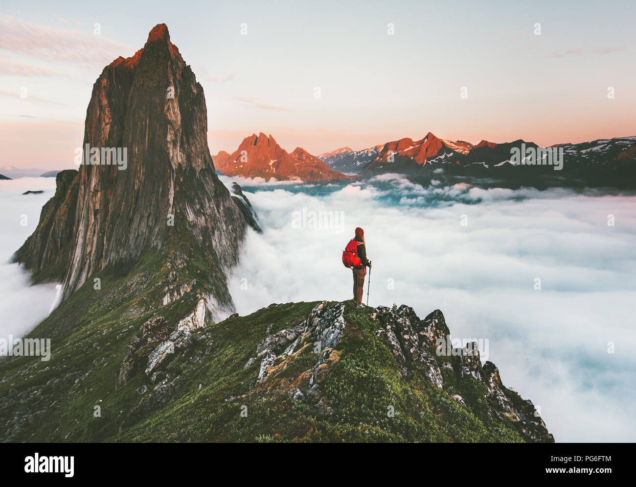 Traveler on cliff over clouds exploring sunset Segla mountain alone hiking adventure journey outdoor Norway vacations traveling lifestyle weekend geta - Stock Image