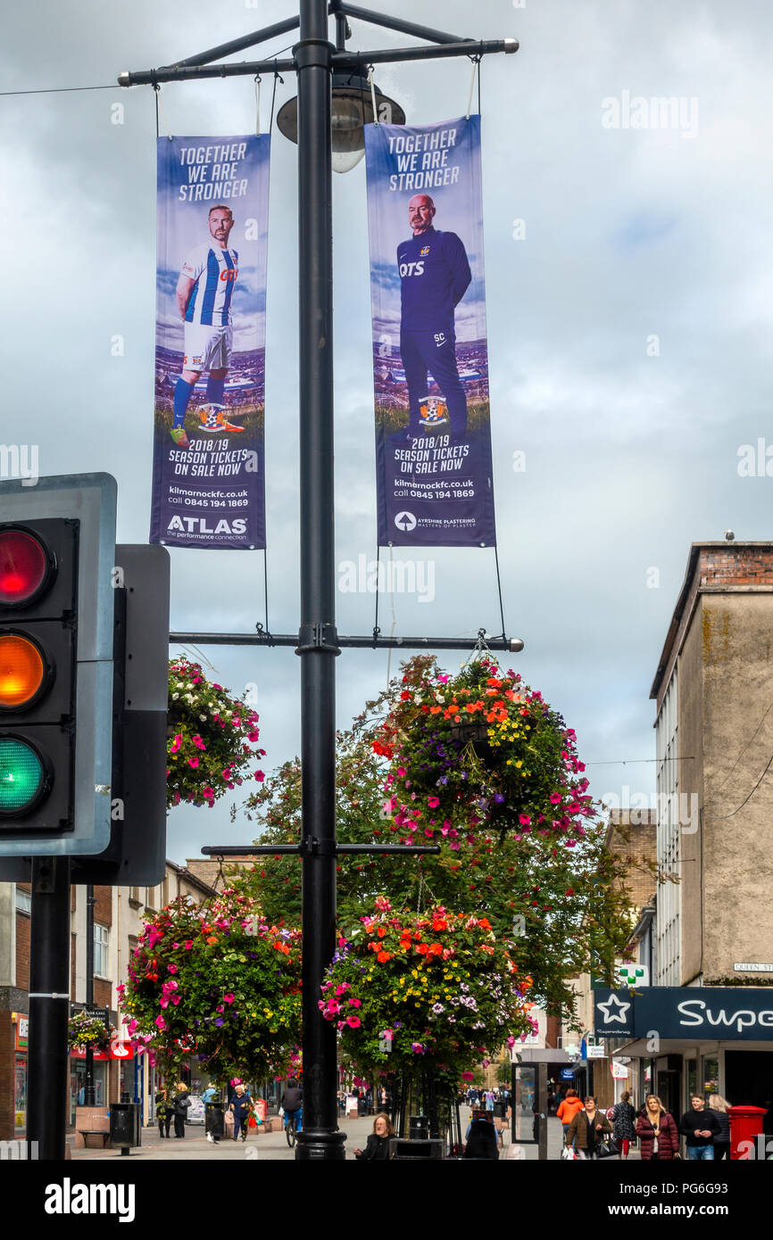 King Street, shopping street in Kilmarnock, East Ayrshire, Scotland, with hanging baskets and banners advertising season tickets for Kilmarnock FC - Stock Image