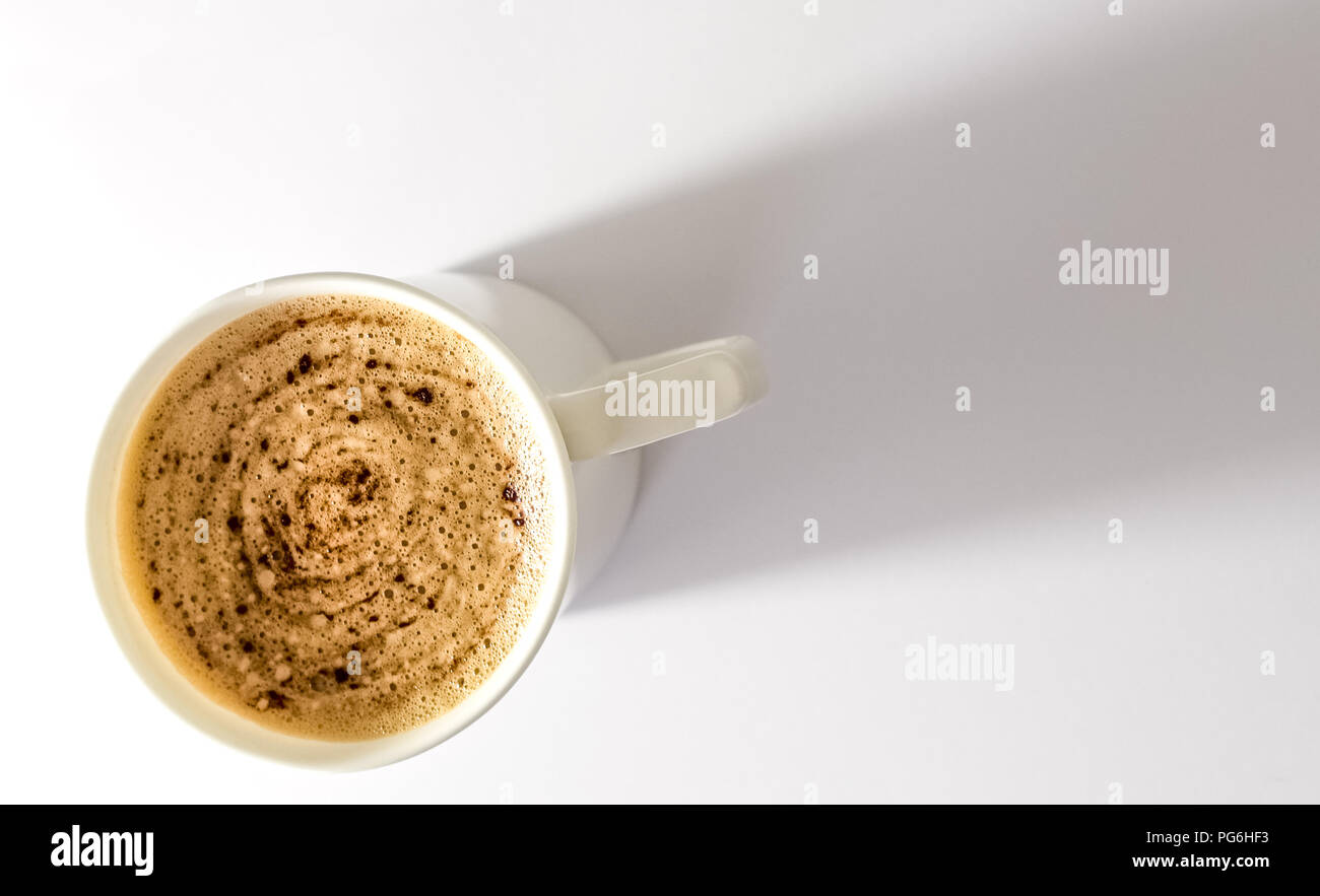 White Mug of Cappucino on White background. Mug of coffe on the lower left of the image with plenty of room for text. - Stock Image