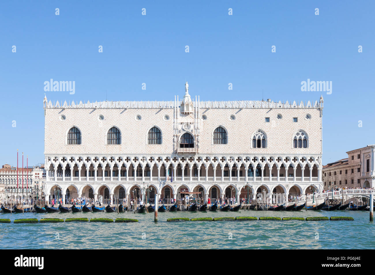 Doges Palace, Palazzo Ducale, Ducal Palace, San Marco, Venice, Veneto, Italy in morning light from the lagoon with gondolas and tourists, blue sunny s - Stock Image