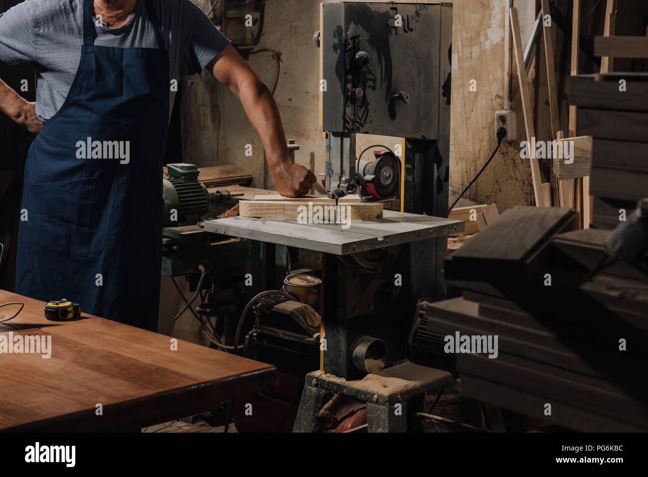 partial view of woodworker standing near electric drill at wooden workshop - Stock Image