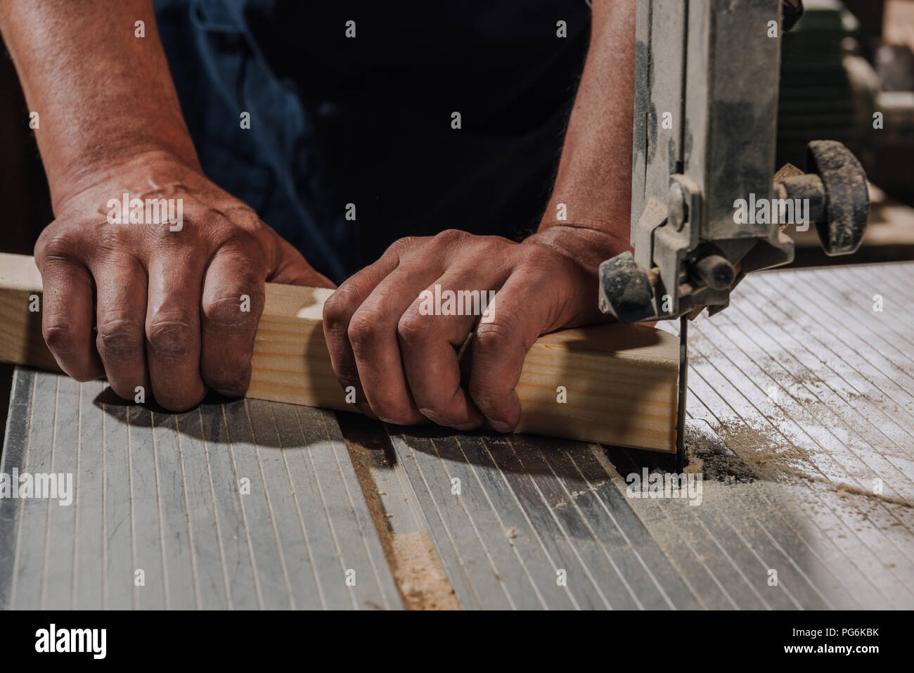 partial view of woodworker using electric drill on wood at workshop - Stock Image