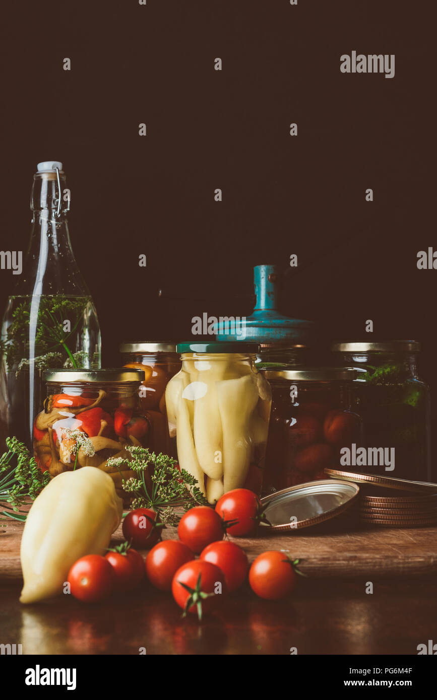 glass jars with preserved vegetables and fresh vegetables on table - Stock Image